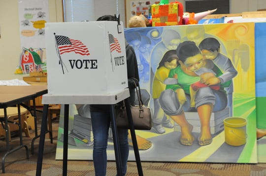 A woman casts her ballot at Sherwood Elementary School in Salinas on Election Day, with artwork from Jose Ortiz's Hijos del Sol Arts Productions serving as the backdrop.