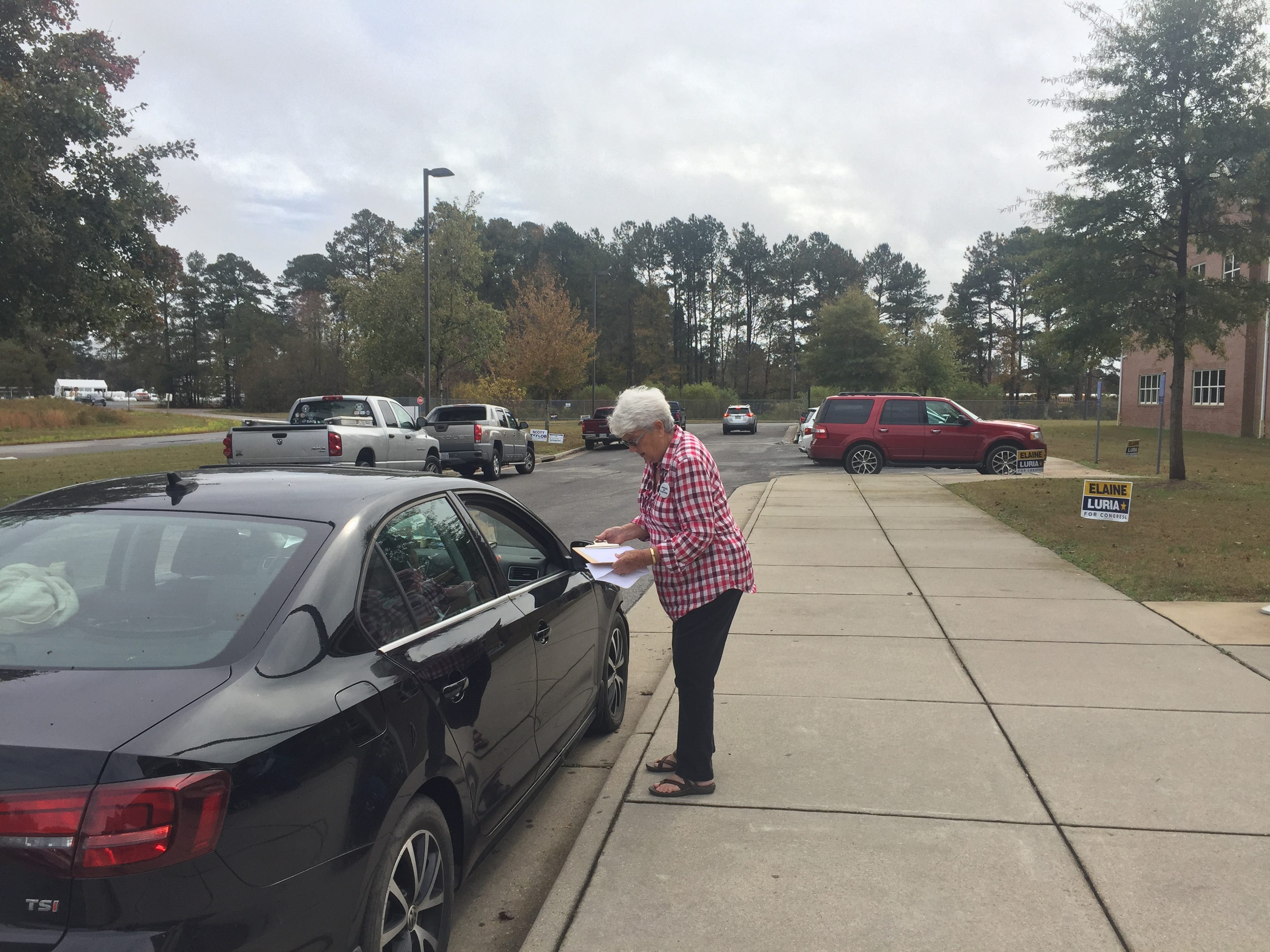 Election officer Peggy Brown assists a voter to cast a ballot at the curbside at Nandua Middle School in Onley, Virginia on Tuesday, Nov. 6, 2018.