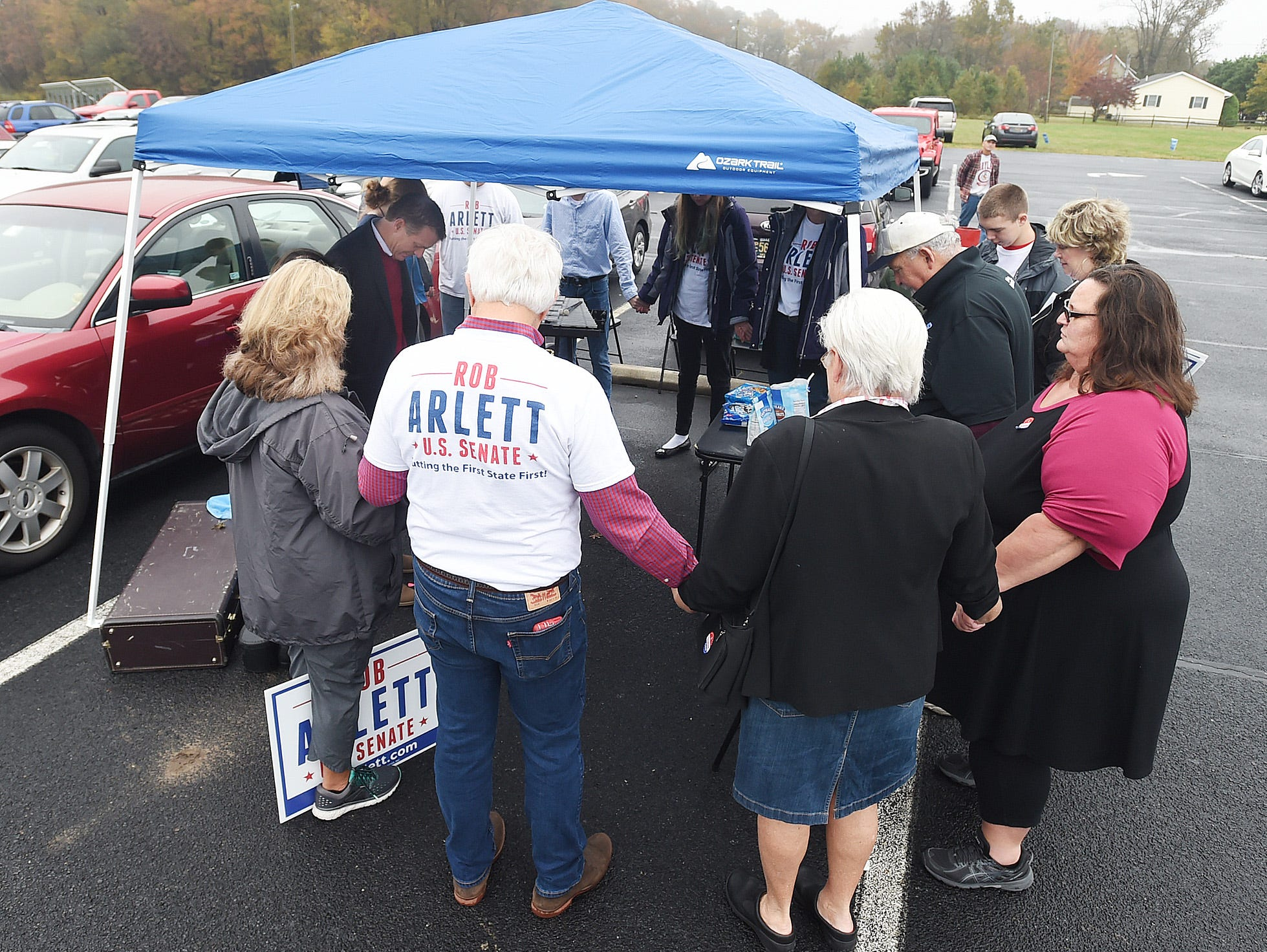 U.S. Senate Candidate Rob Arlett and supporters hold a prayer prior to voting at the Roxana Fire Station as voter turnout in eastern Sussex County has been steady at polling places in Rehoboth, Roxana, and Angola as candidates still greet supporters for their support.