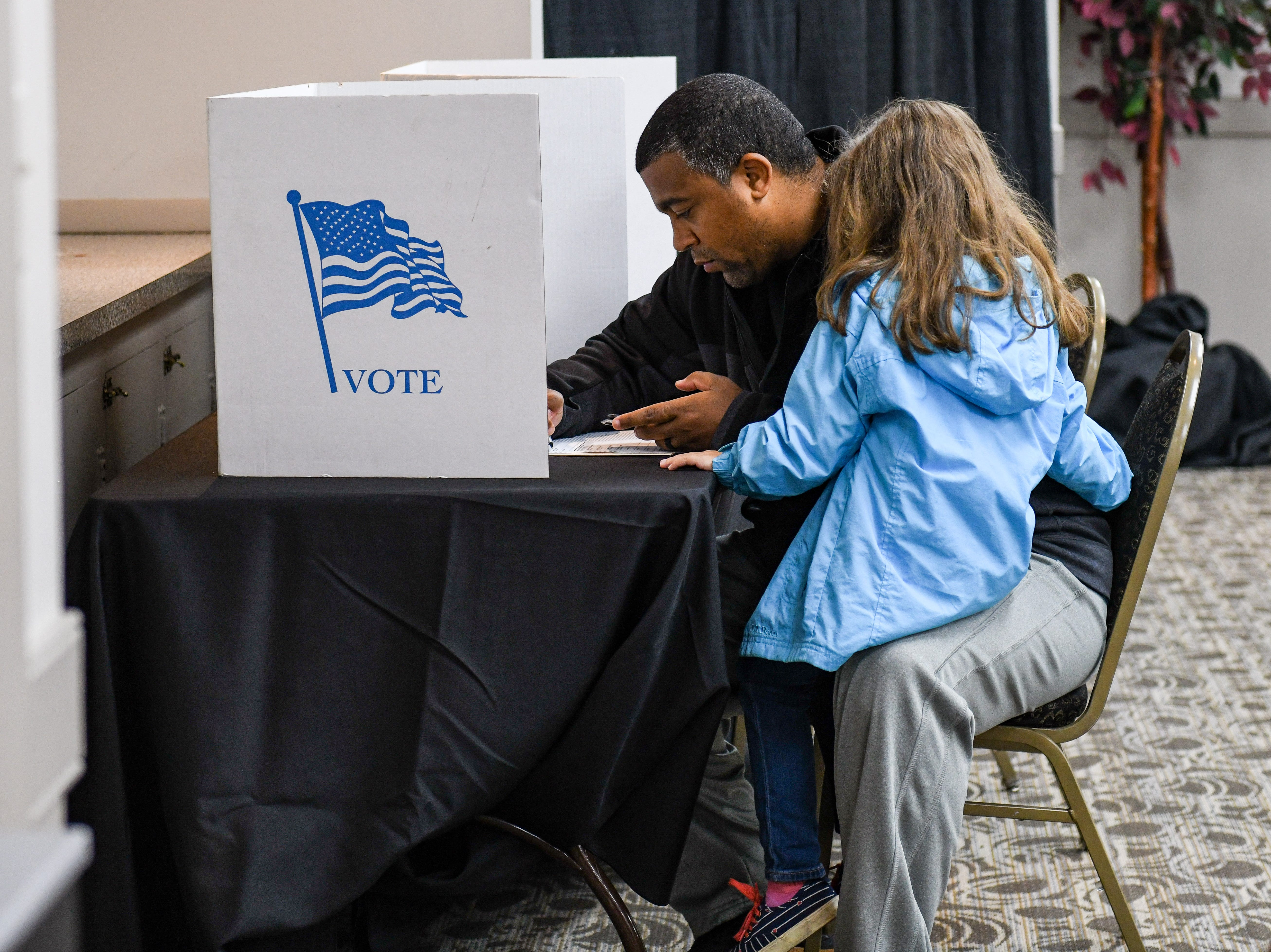 Cameron Ball votes in the midterm election with his daughter on his lap at the Wicomico Civic Center on Tuesday, Nov 6, 2018.