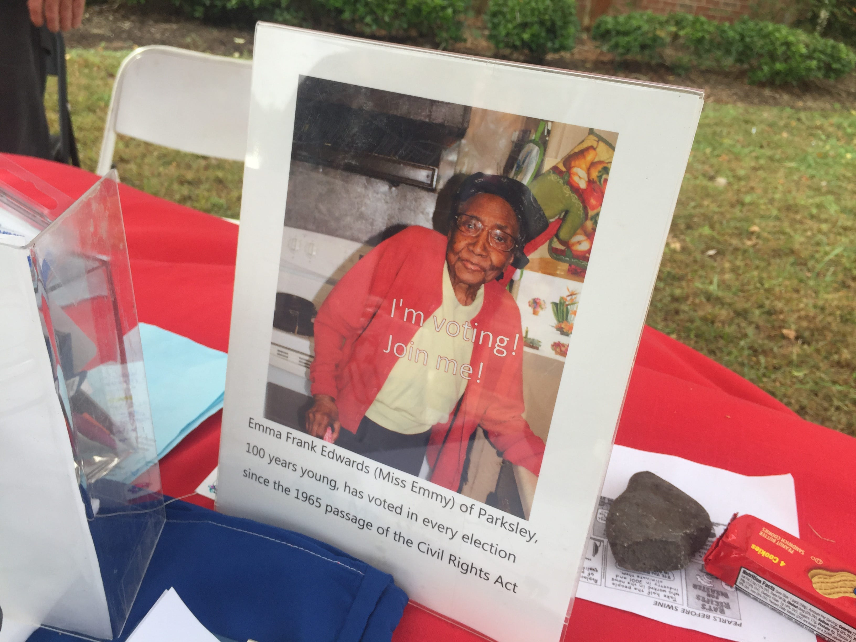 A photograph of Emma Frank Edwards, 100, of Parksley, who has voted in every election since the 1965 passage of the Civil Rights Act, is displayed at a table staffed by volunteers for the Democratic candidates outside the polling place at Nandua Middle School in Onley, Virginia on Tuesday, Nov. 6, 2018.