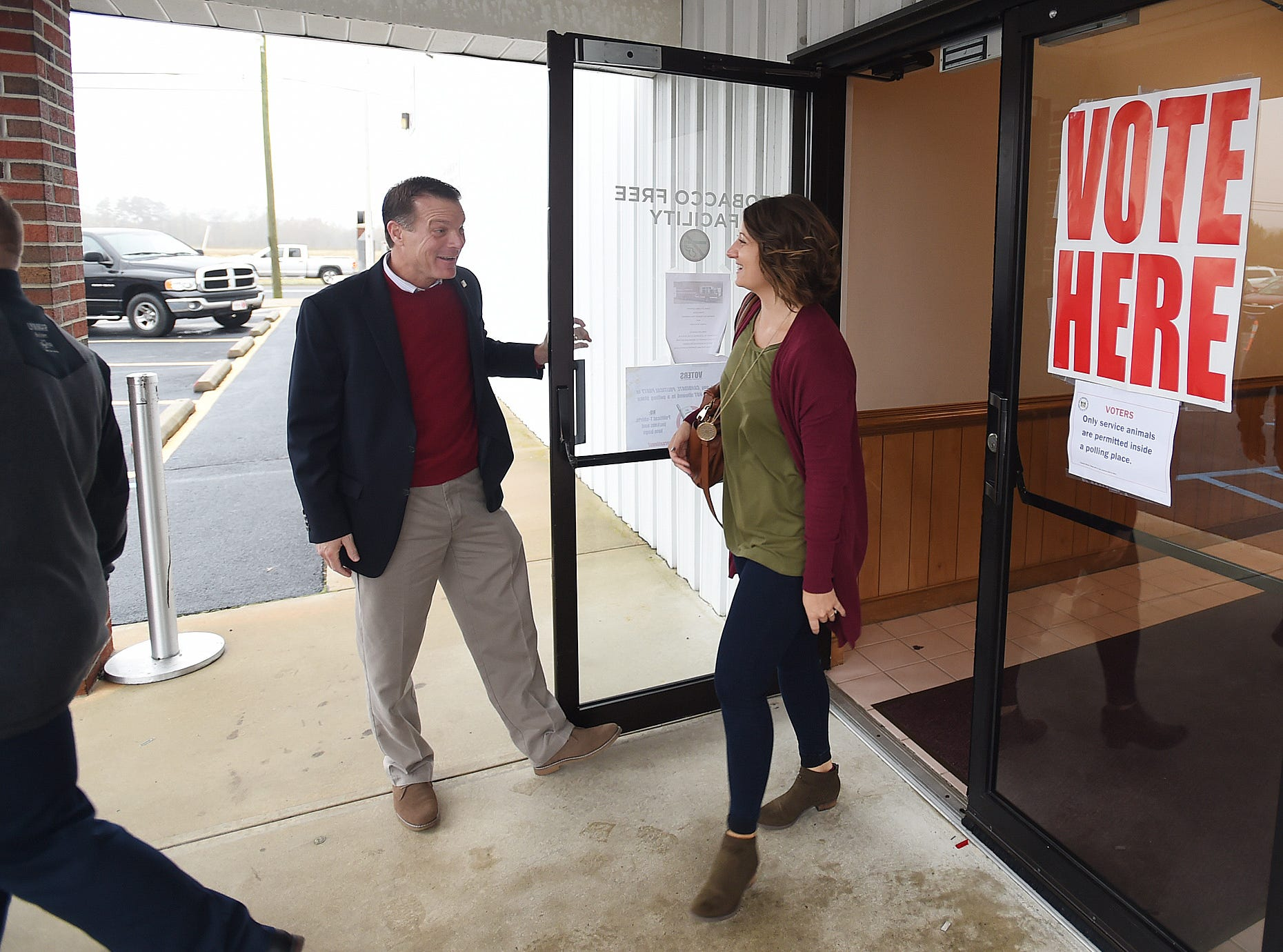 U.S. Senate Candidate Rob Arlett holds the door for voters at the Roxana Fire Station as voter turnout in eastern Sussex County has been steady at polling places in Rehoboth, Roxana, and Angola as candidates still greet supporters for their support.