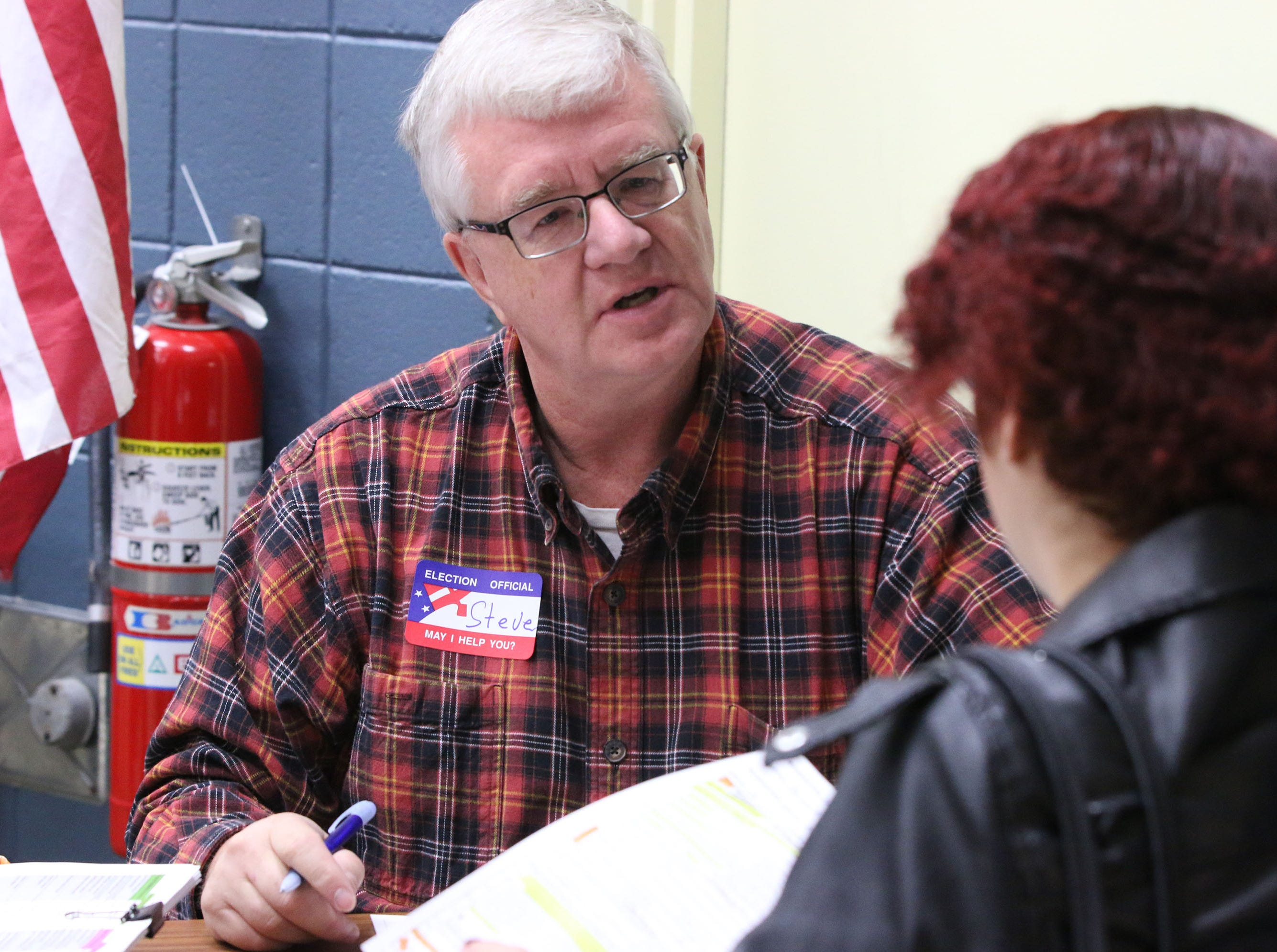 Poll worker Steve Weina, left, explains voter registration instructions to a voter, Tuesday, November 6, 2018, in Sheboygan, Wis.