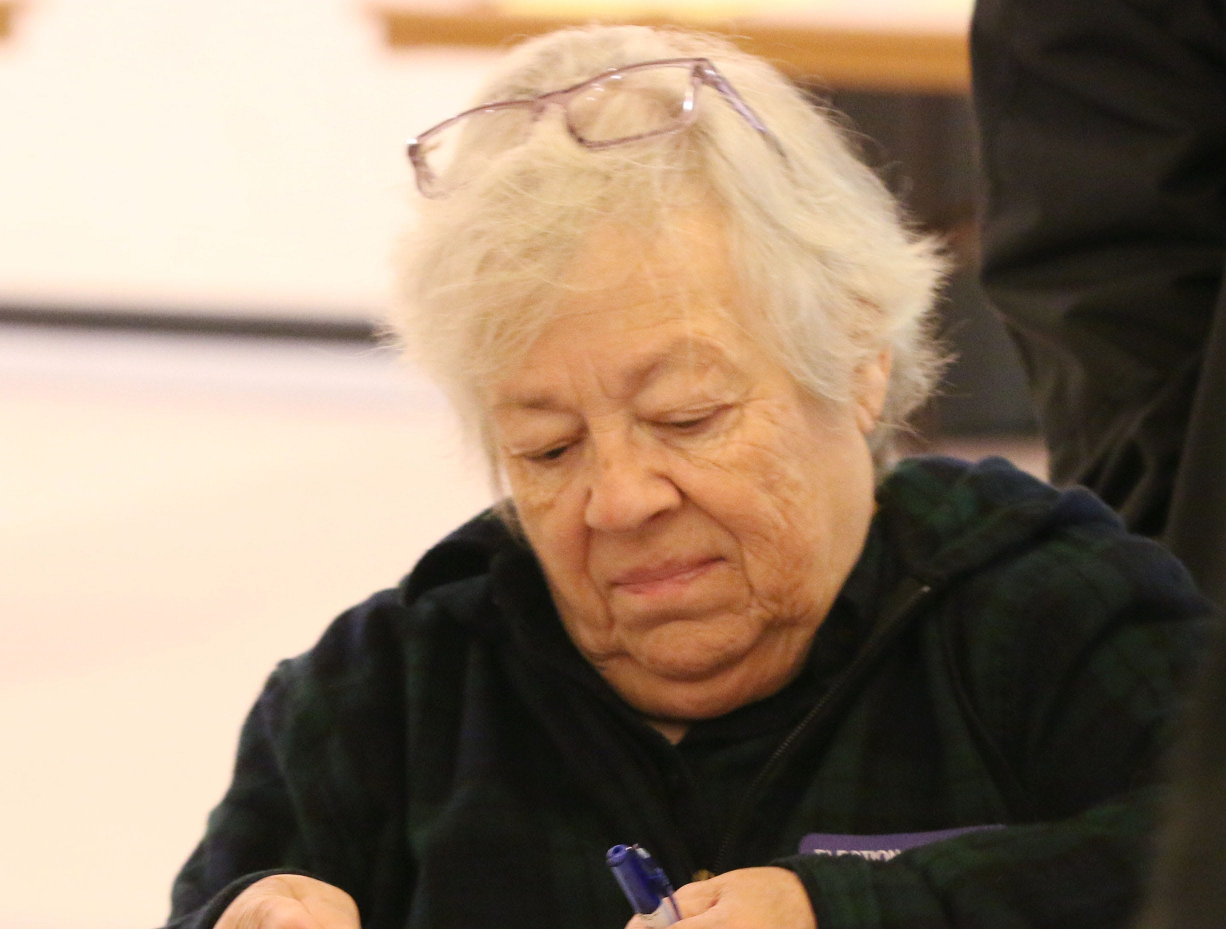 Poll worker Mary Jo Beniger thumbs through a voter list at the First United Lutheran Church poll, Tuesday, November 6, 2018, in Sheboygan, Wis.