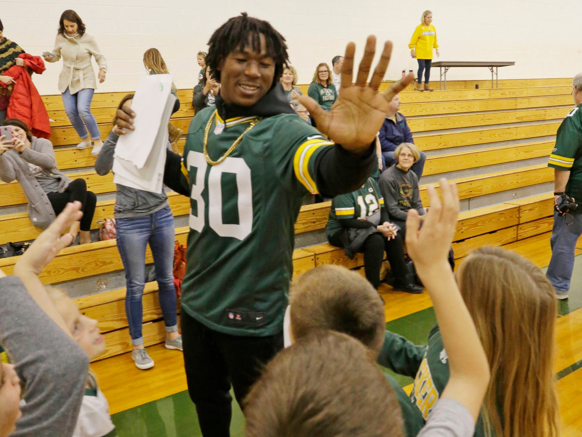 Green Bay Packer Jamaal Williams gives a high five to school children from Plymouth's St. John the Baptist Catholic School, Tuesday, November 6, 2018, in Plymouth, Wis.