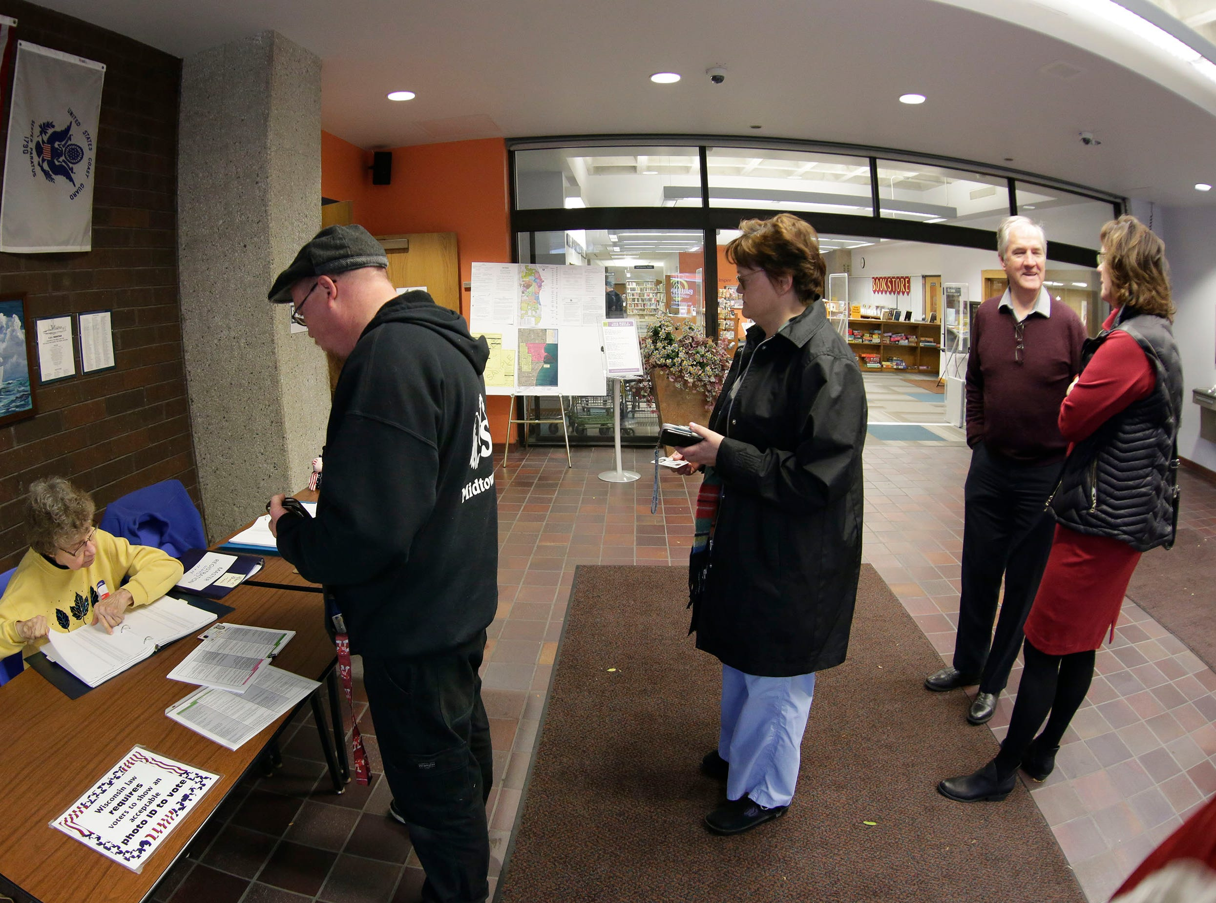 Poll worker Sue Wisse, checks over where a voter needs to vote at Mead Public Library polling place, Tuesday, November 6, 2018, in Sheboygan, Wis.