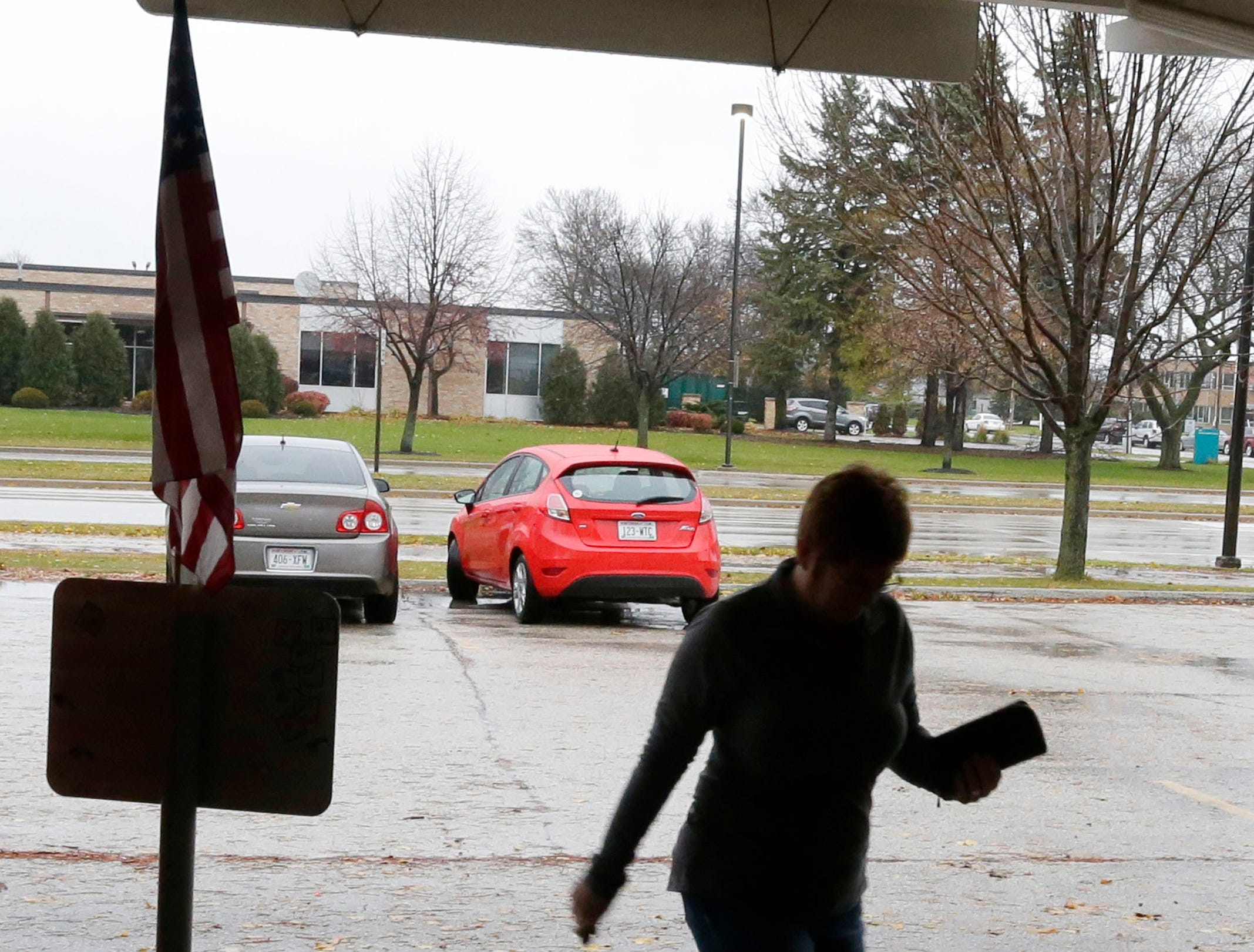 A woman in silhouette walks briskly to the voting entrance at First United Lutheran, Tuesday, November 6, 2018, in Sheboygan, Wis.