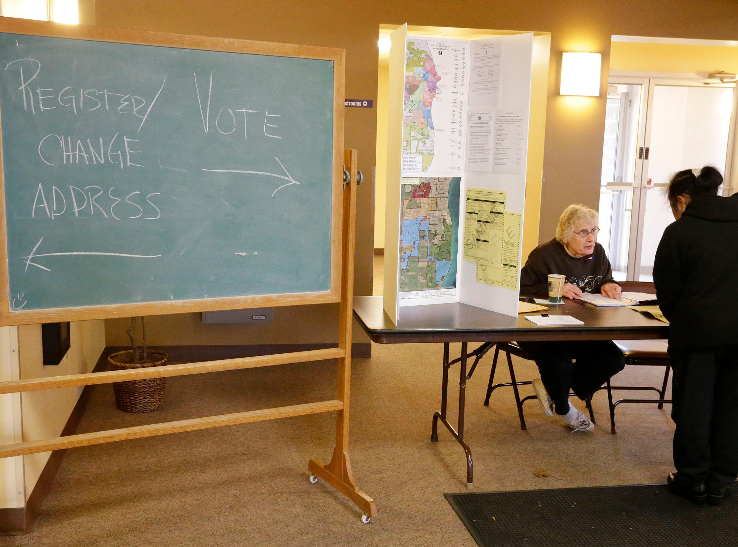 A chalk board helps direct voters where they need to go at Good Shepard Lutheran Church, Tuesday, November 6, 2018, in Sheboygan, Wis.