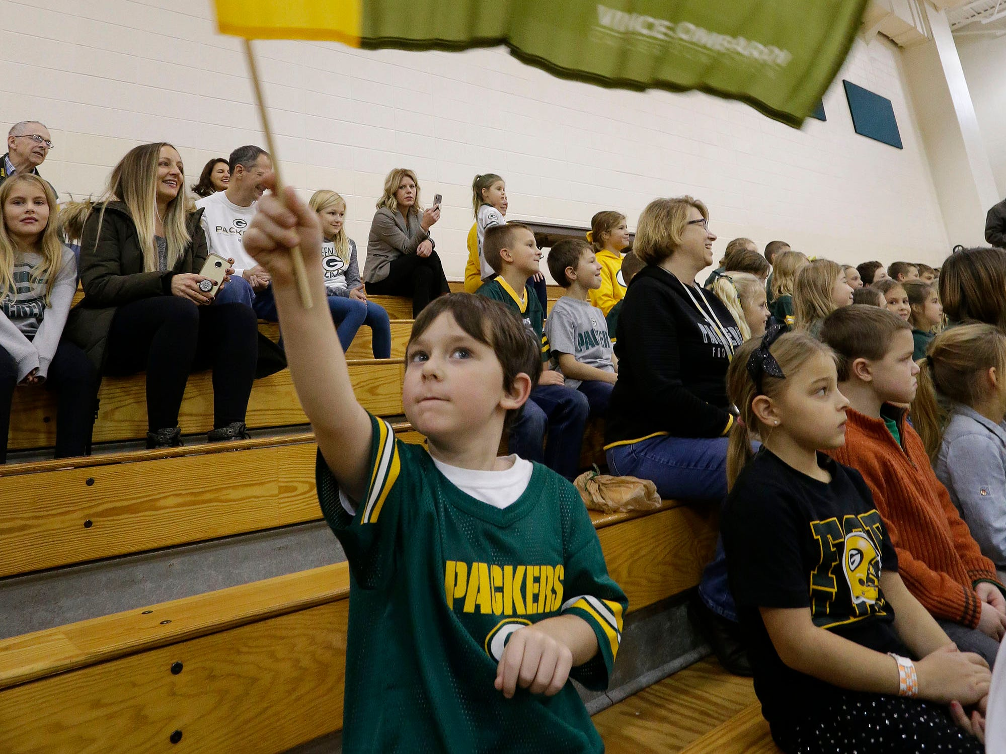 Timothy Barnes, 5, waves a Green Bay Packer banner in honor of Packer Jamaal Williams visit to Plymouth's St. John the Baptist Catholic School, Tuesday, November 6, 2018, in Plymouth, Wis.
