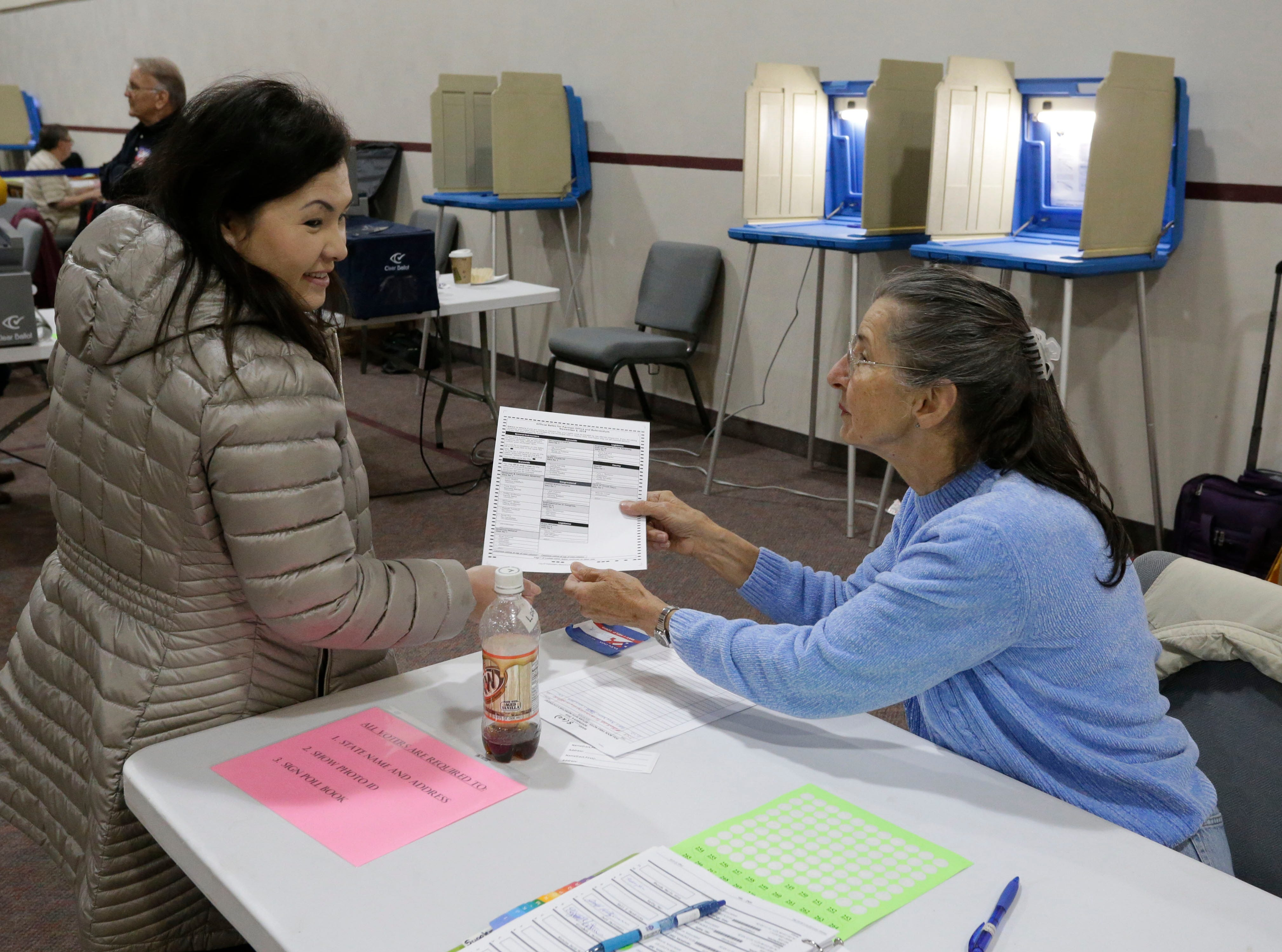 Kathy Her, left, receives a blank ballot from poll worker Loretta Wissbroecker at Evangelical Free Church polls, Tuesday, November 6, 2018, in Sheboygan, Wis.
