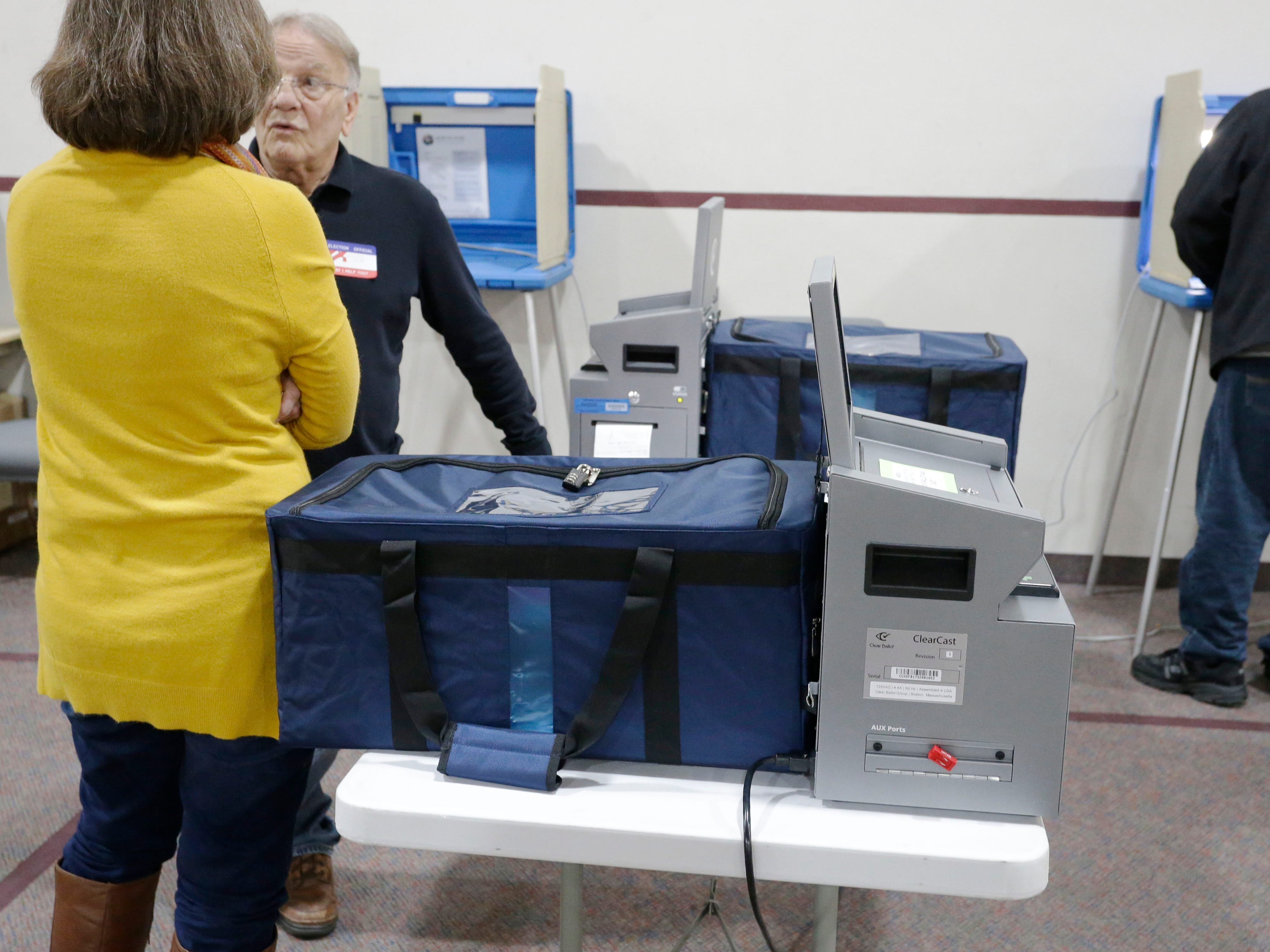Poll workers stand near one of the new Sheboygan County-wide voting tabulators as seen at Evangelical Free Church polls, Tuesday, November 6, 2018, in Sheboygan, Wis.
