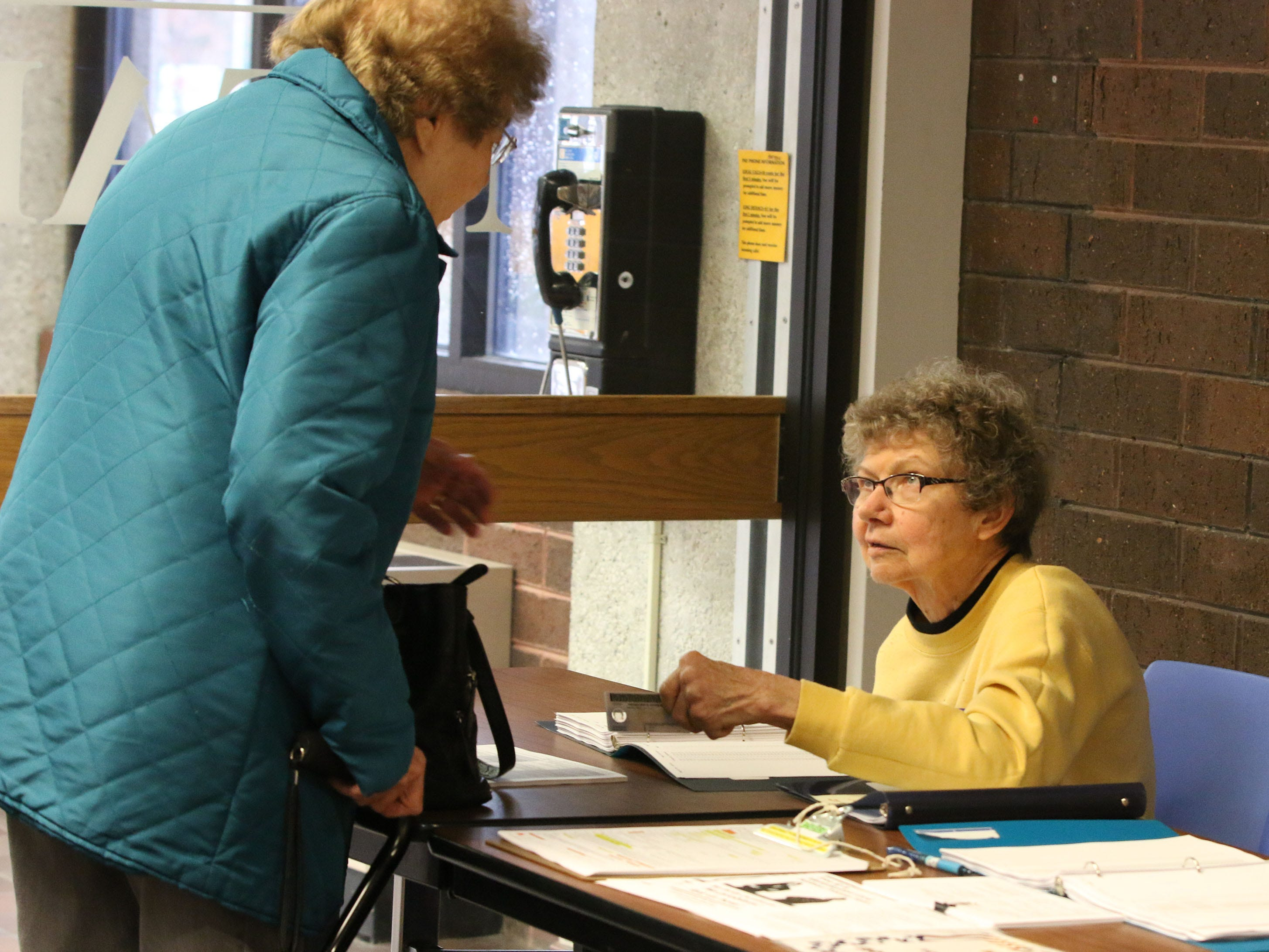 Poll worker Sue Wisse, assists a voter at Mead Public Library polling place, Tuesday, November 6, 2018, in Sheboygan, Wis.