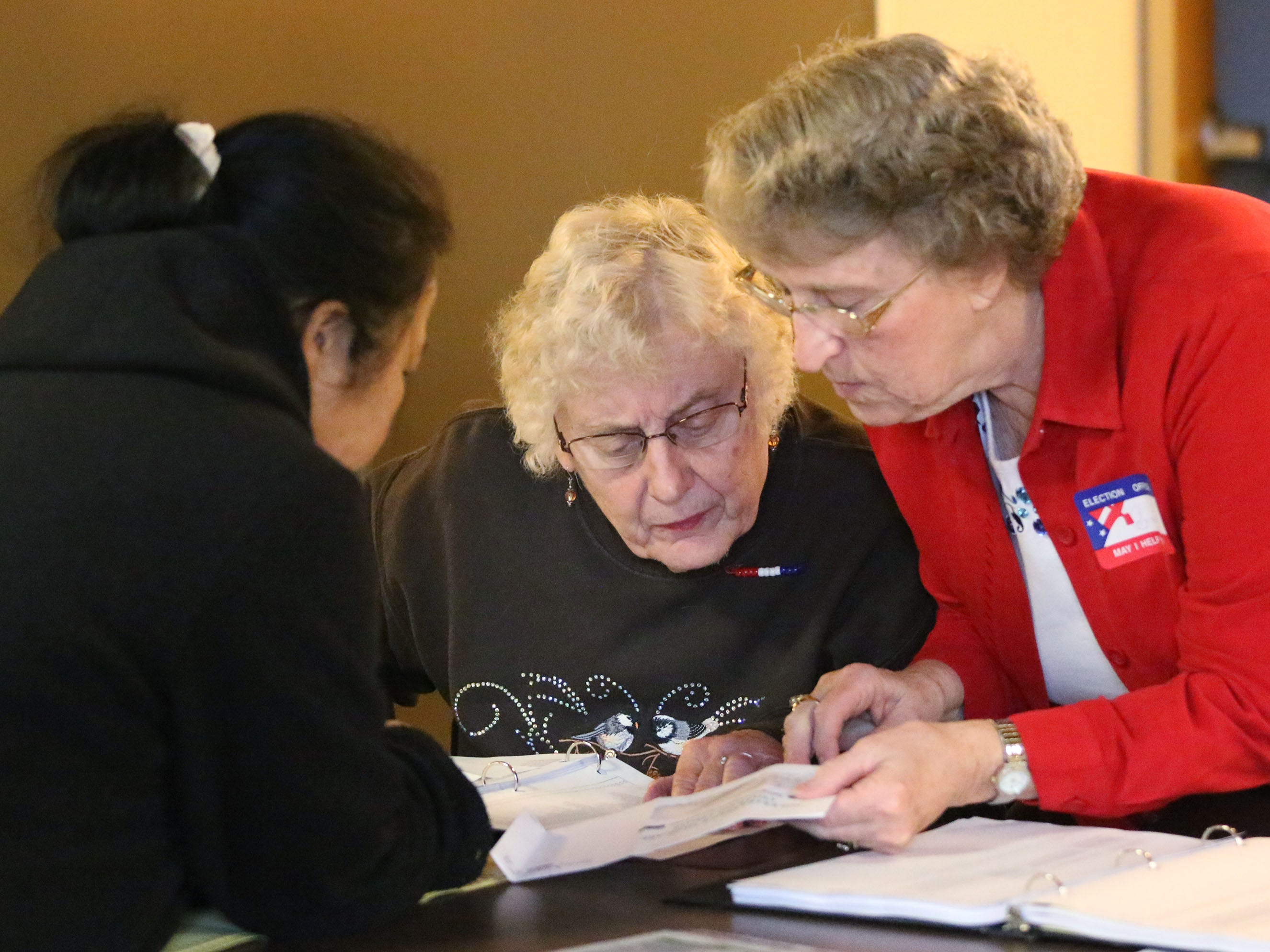 Bao Vue, of Sheboygan, left, gets help on voting from poll workers Cynthia Kuester, left, and Connie Knop, at Bethany Reformed Church, Tuesday, November 6, 2018, in Sheboygan, Wis.