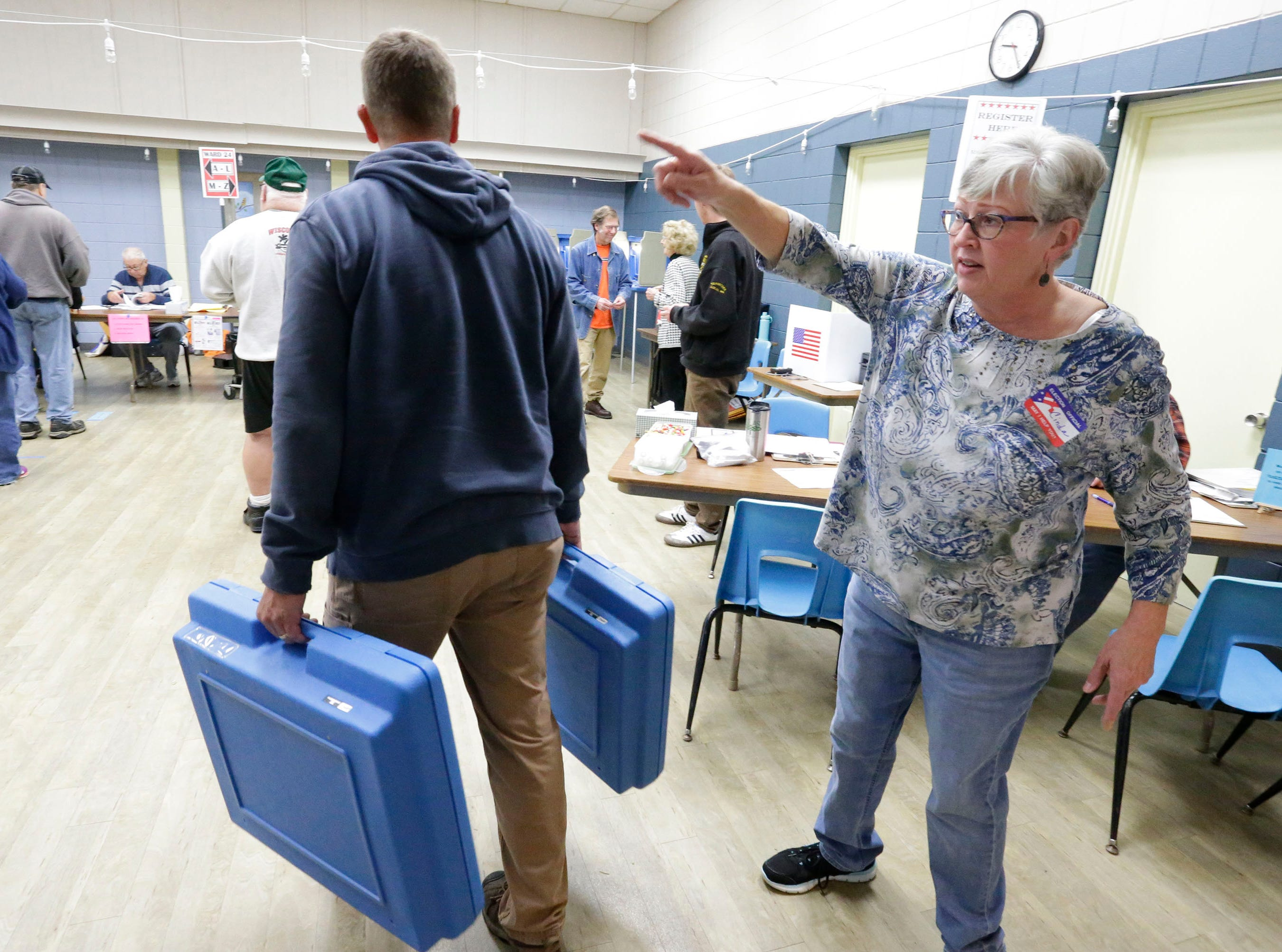 Poll worker Cinda Langhoff, right, directs a city employee where to set up additional polling stations at the Senior Activity Center, Tuesday, November 6, 2018, in Sheboygan, Wis.