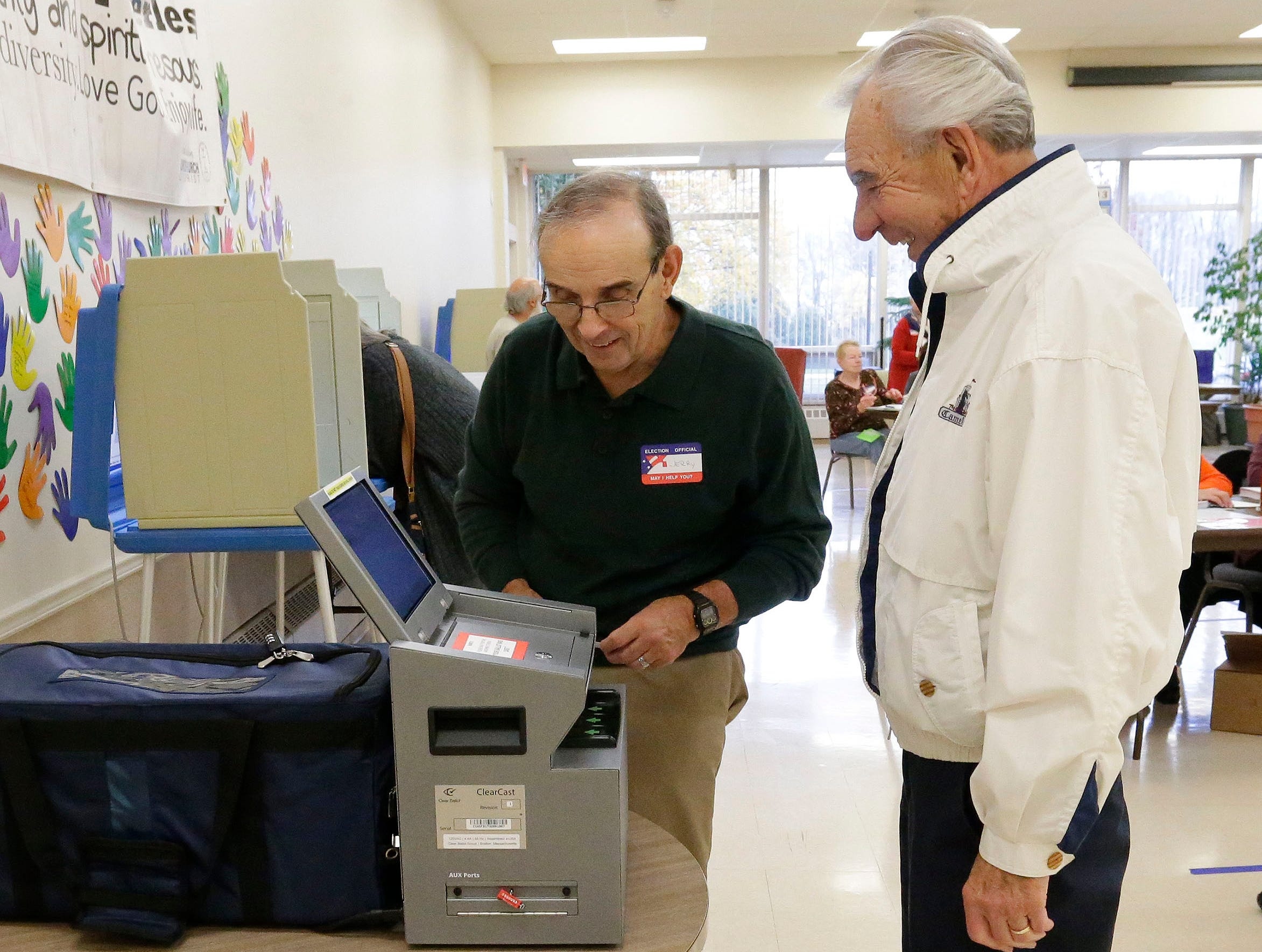 Poll worker Jerry Cramelt, left, instructs Jerry Pantel, right, how to correctly place his ballot in the box at the First Congregational Church poll, Tuesday, November 6, 2018, in Sheboygan, Wis.