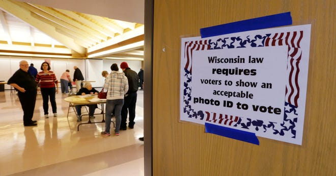 A sign instructs voters that they need an approved photo ID in order to vote, Tuesday, November 6, 2018, in Sheboygan, Wis.