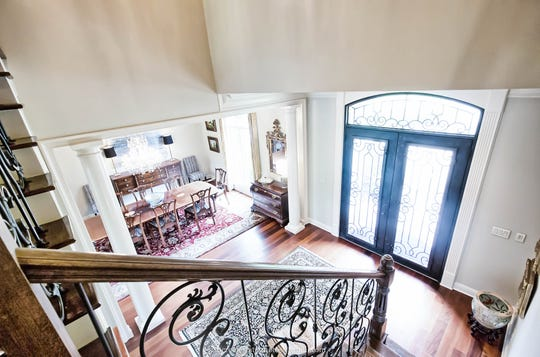 The staircase is a work of art with wooden steps and custom iron work.