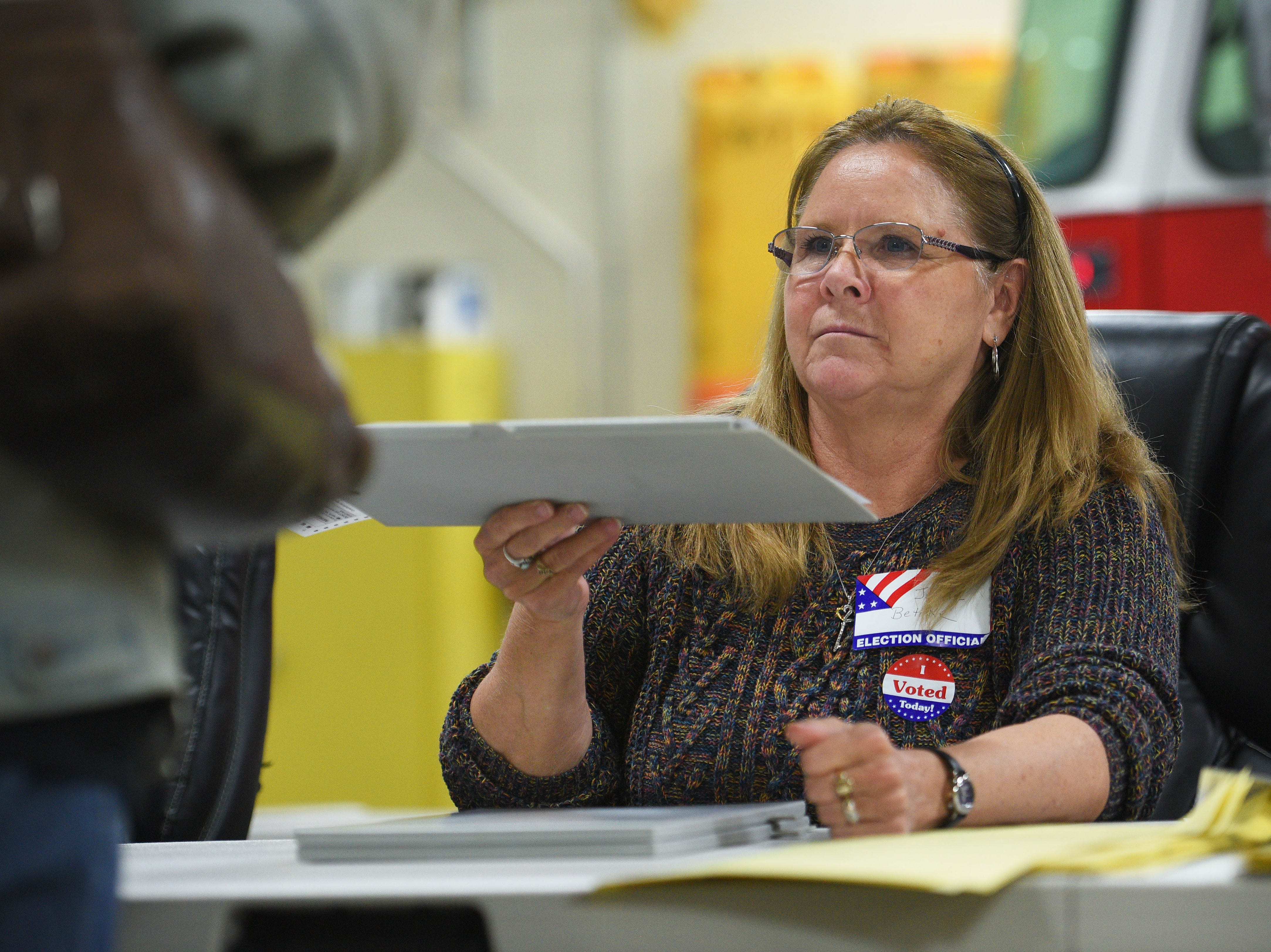 Poll worker Jeanne Bethke hands a ballot out to a voter for the 2018 midterm elections Tuesday, Nov. 6, at Fire Station #7 in Sioux Falls.