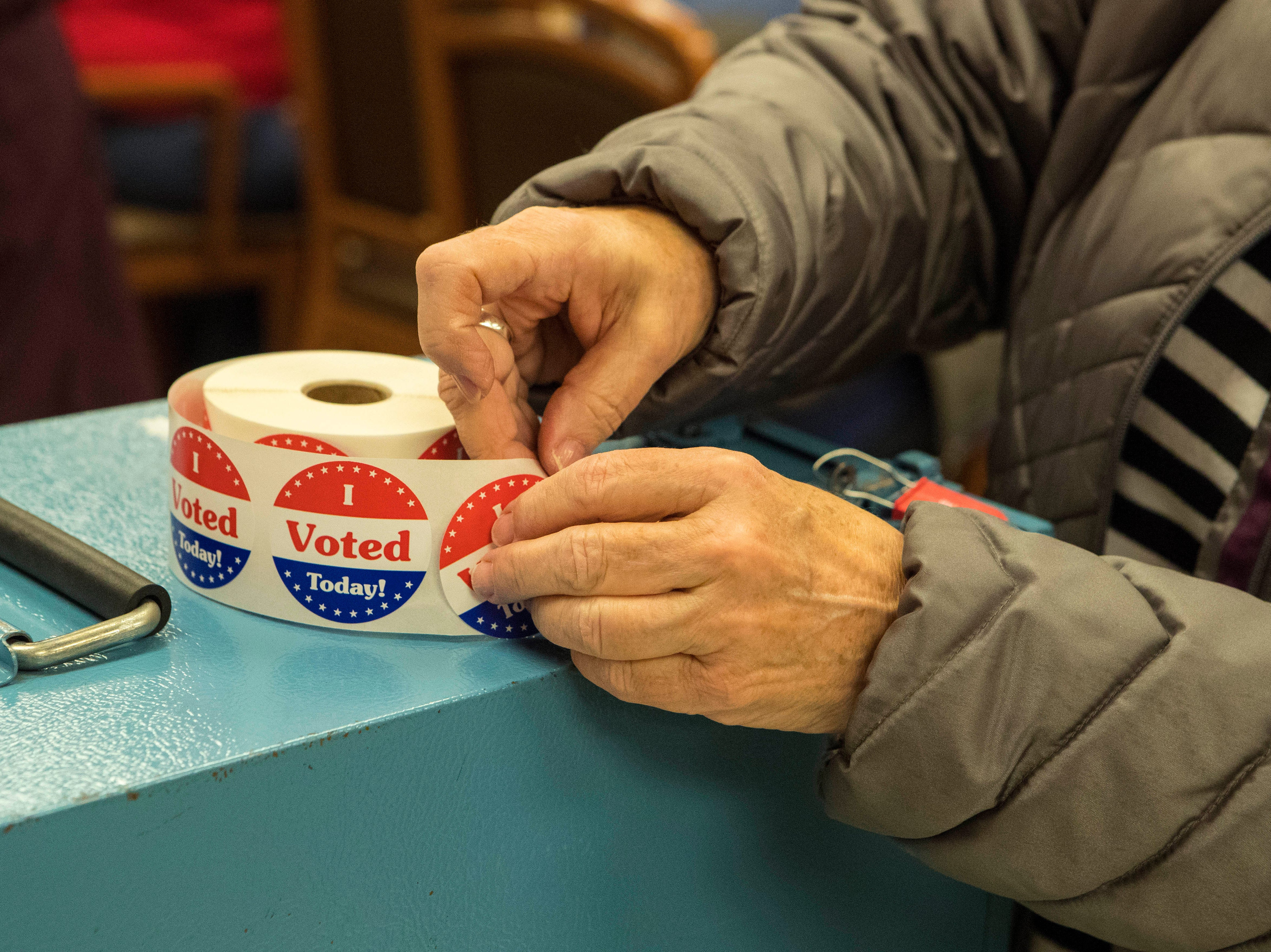 Sioux Falls resident grabs a voting sticker at Avera Prince of Peace Retirement Community in Sioux Falls, S.D., Tuesday, Nov. 6, 2018.