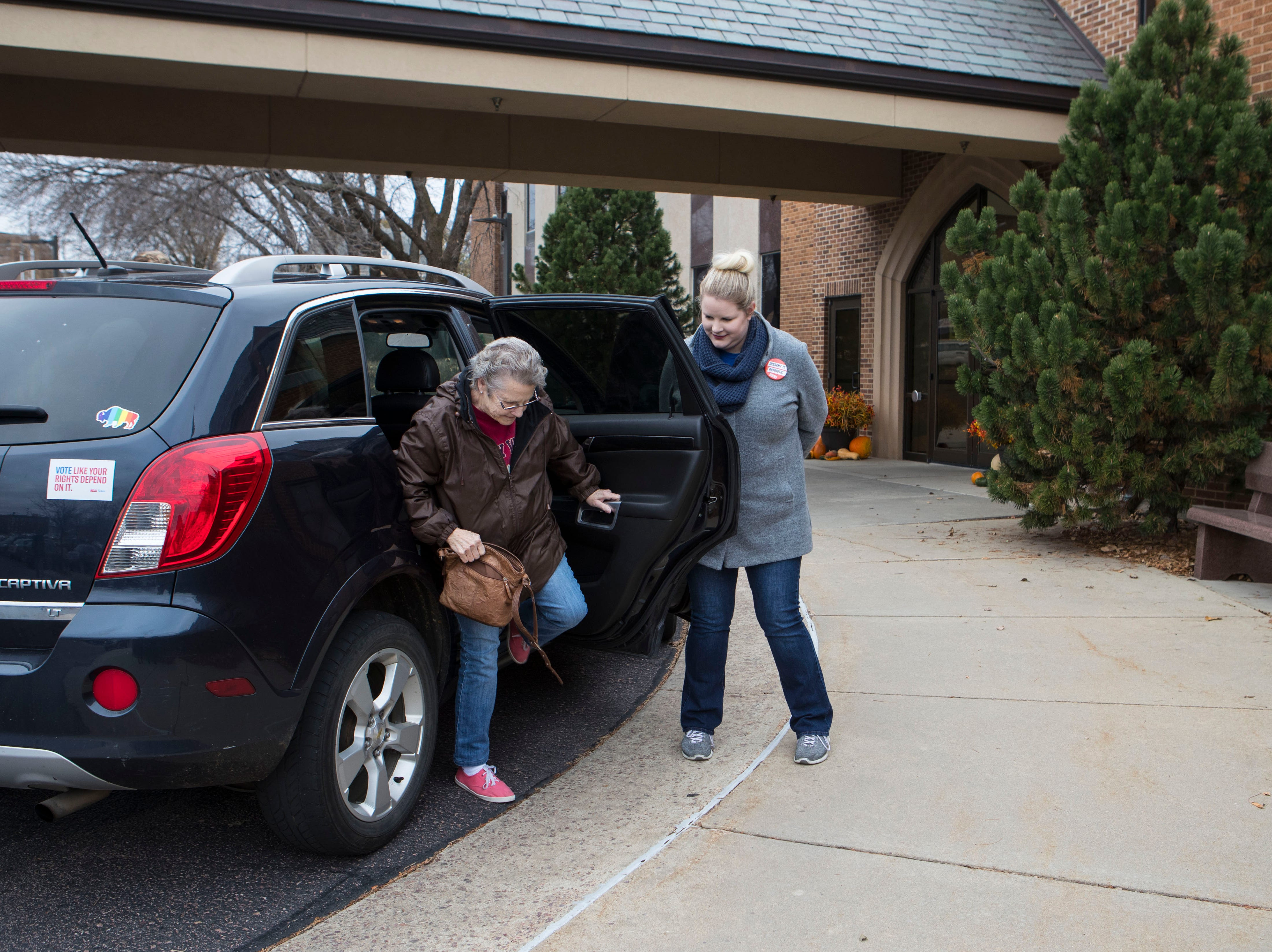 Kirsten Wichern, ACLU volunteer, opens the door for Diana Friedrichs at First Lutheran Church in Sioux Falls, S.D., Tuesday, Nov. 6, 2018. The ACLU is offering free rides to people to their voting centers.
