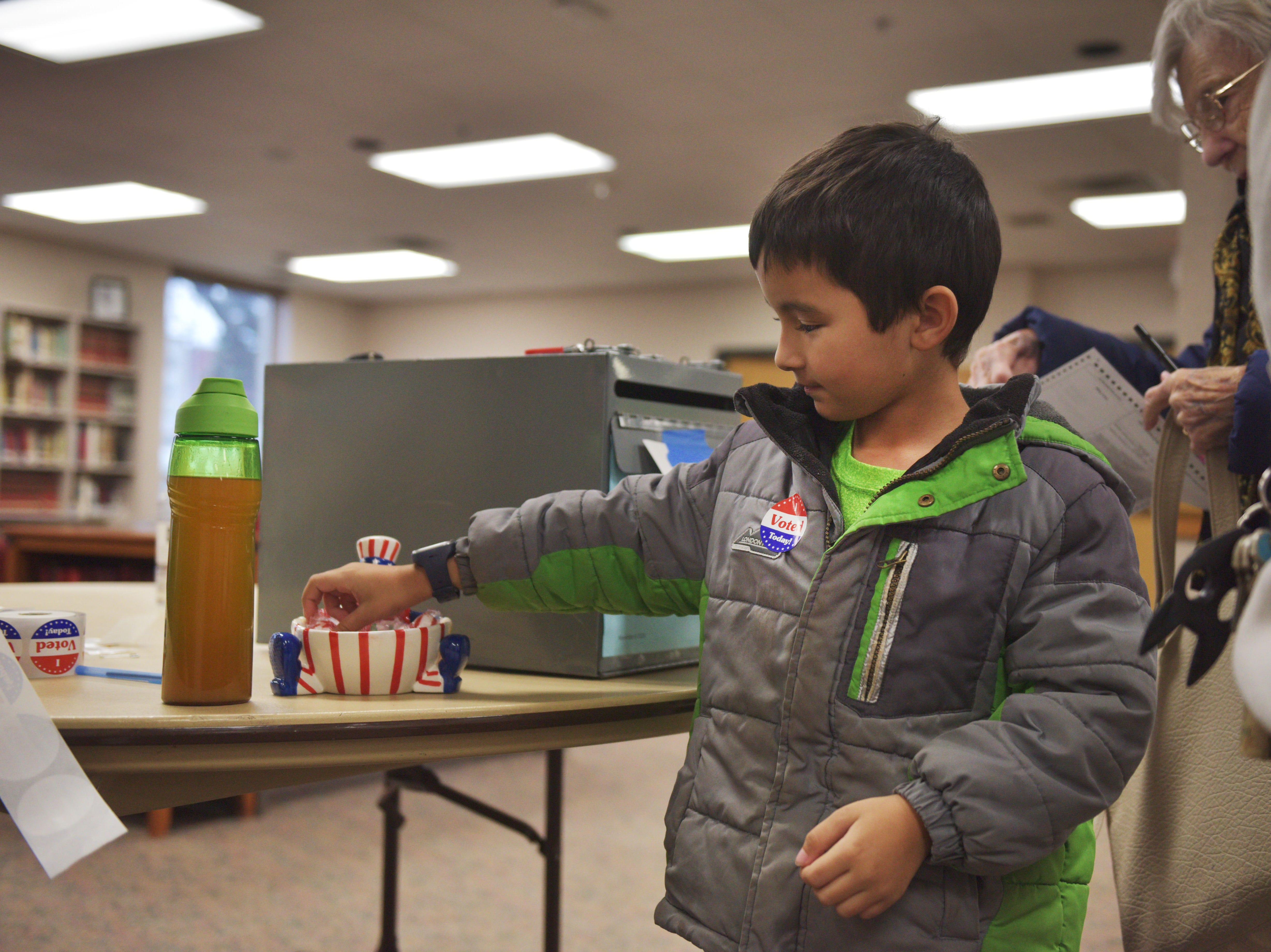 """Maaq Mayo grabs some candy after he gets his """"I voted today!"""" sticker after his mom, Maria Martin, voted in the 2018 midterm elections Tuesday, Nov. 6, at First Lutheran Church in Sioux Falls."""