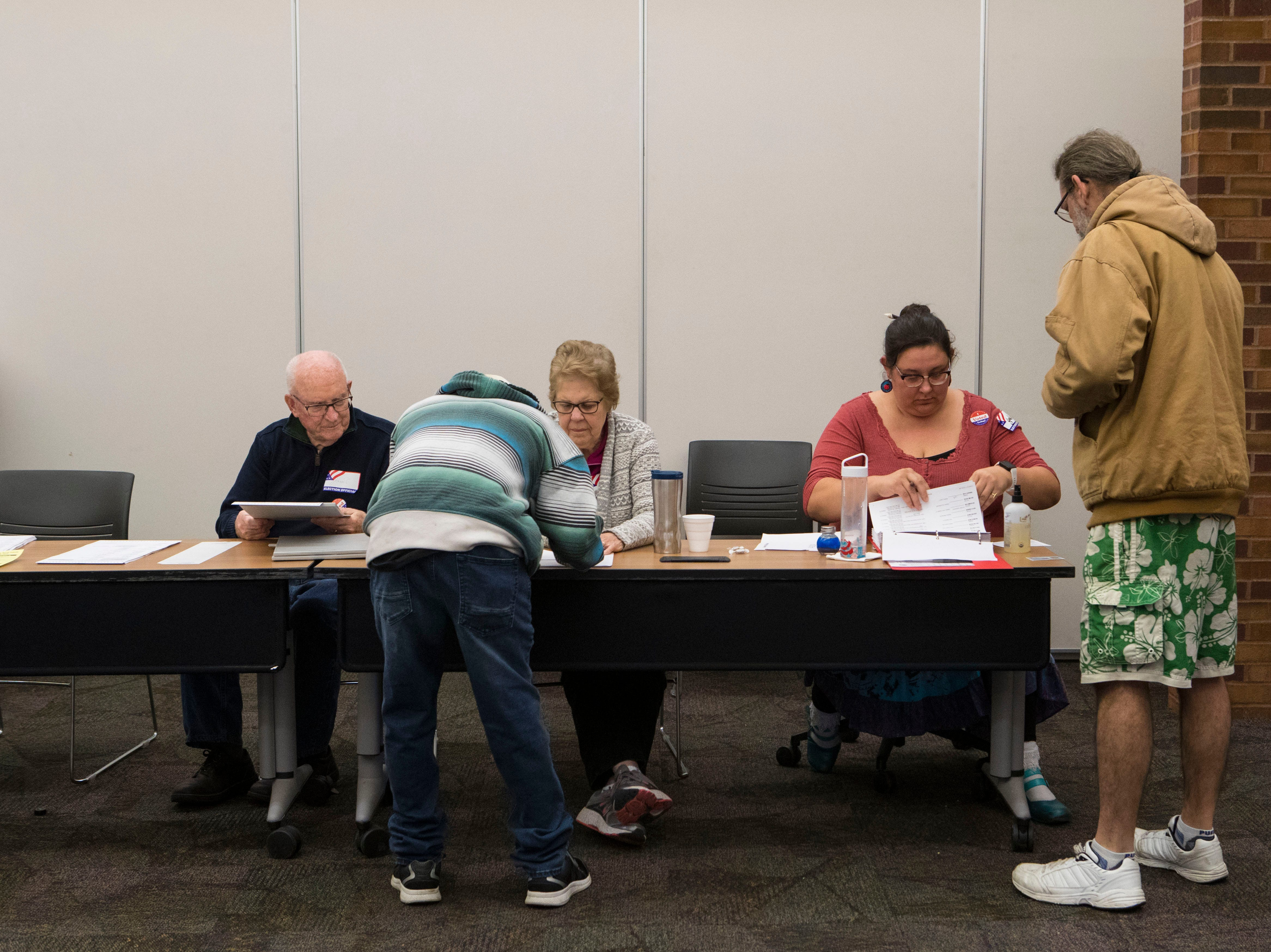 Sioux Falls residents get checked in by election officials at the Downtown branch of the Siouxland Libraries in Sioux Falls, S.D., Tuesday, Nov. 6, 2018.