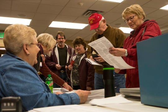 Voters get checked in by election officials at Avera Prince of Peace Retirement Community in Sioux Falls, S.D., Tuesday, Nov. 6, 2018.