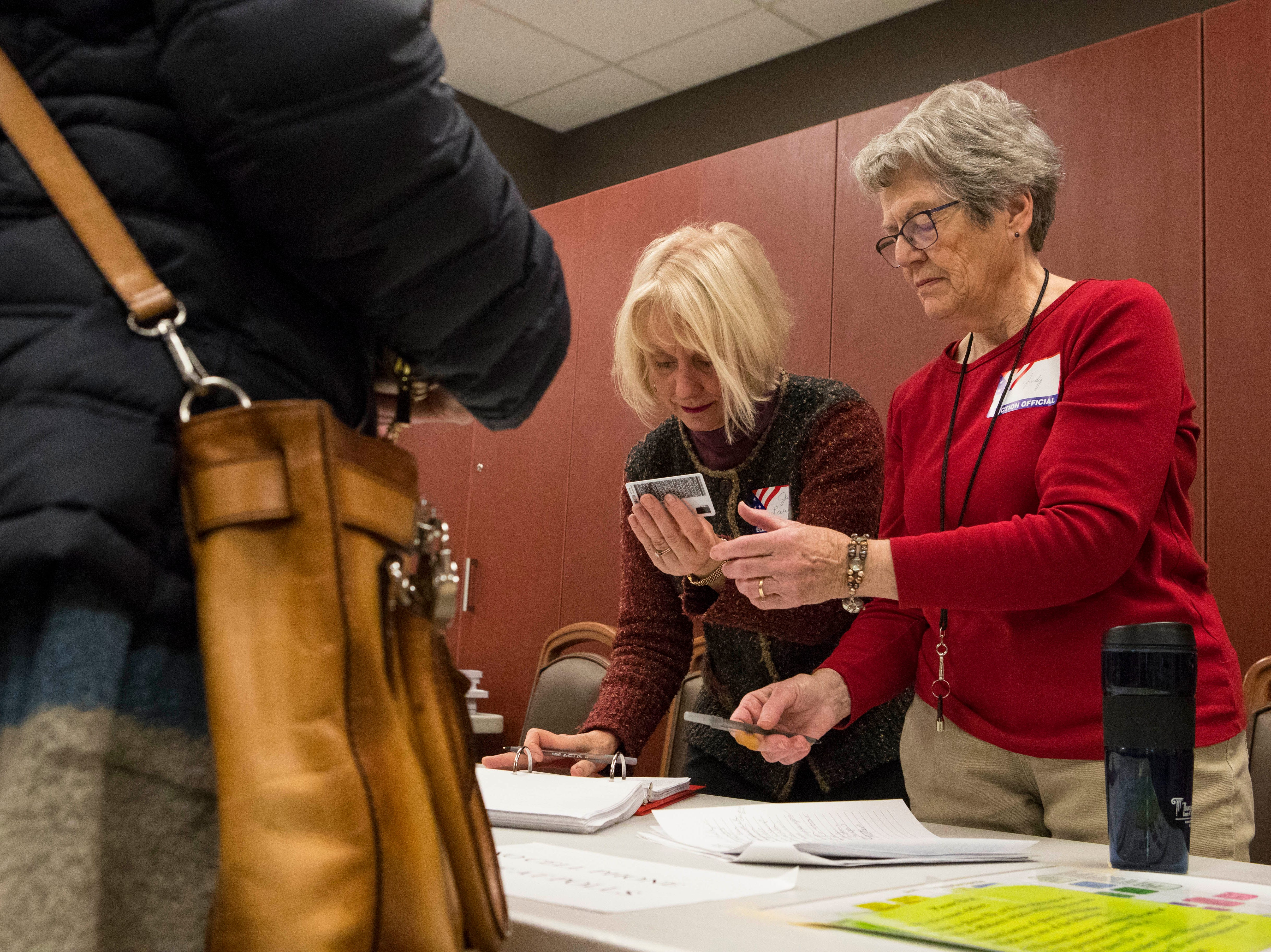 Judy Martin (right) and Julie Larson check in voters at Avera Prince of Peace Retirement Community in Sioux Falls, S.D., Tuesday, Nov. 6, 2018.