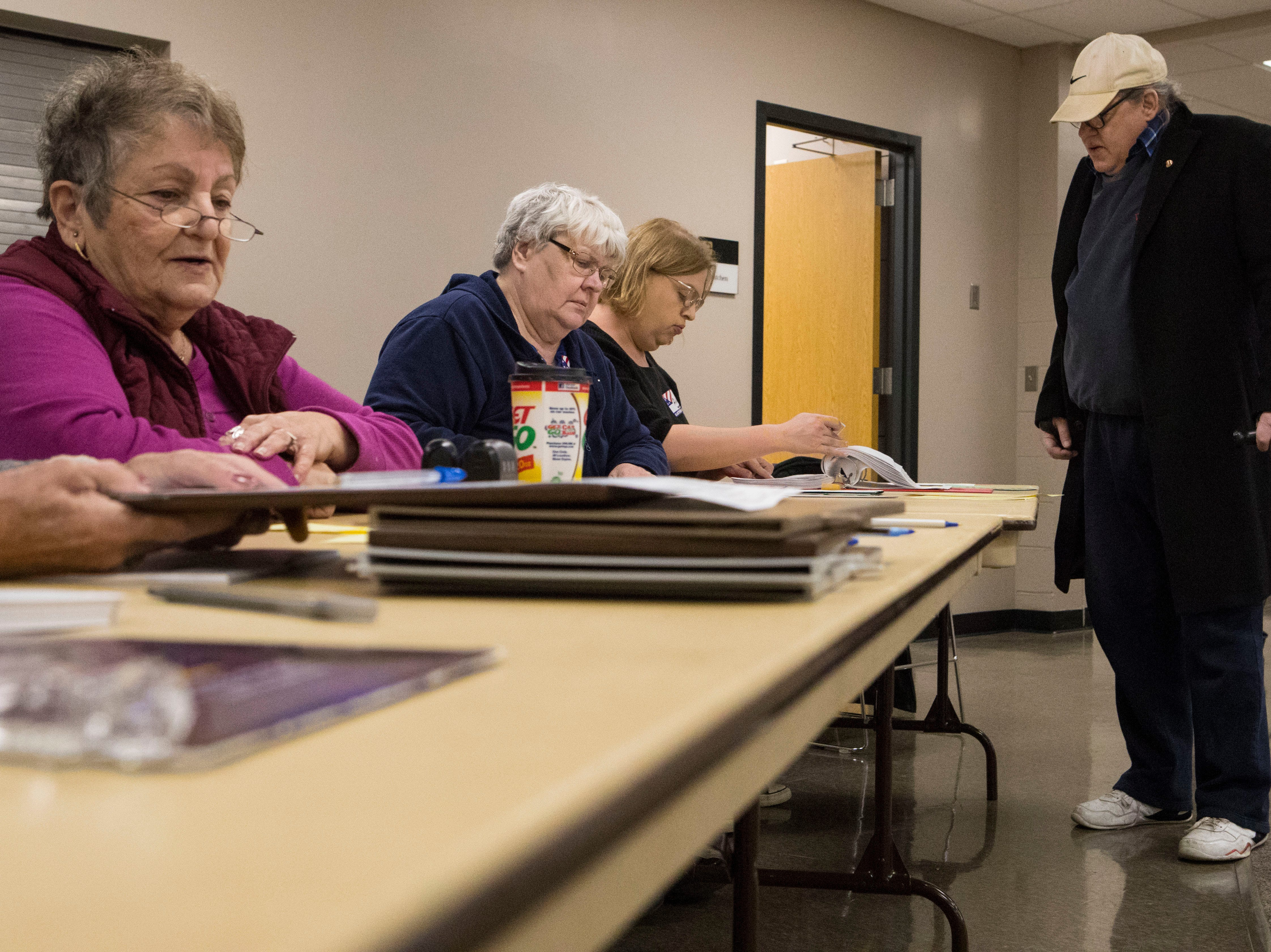 Larry Loebig gets checked in by election officials at First Lutheran Church in Sioux Falls, S.D., Tuesday, Nov. 6, 2018.