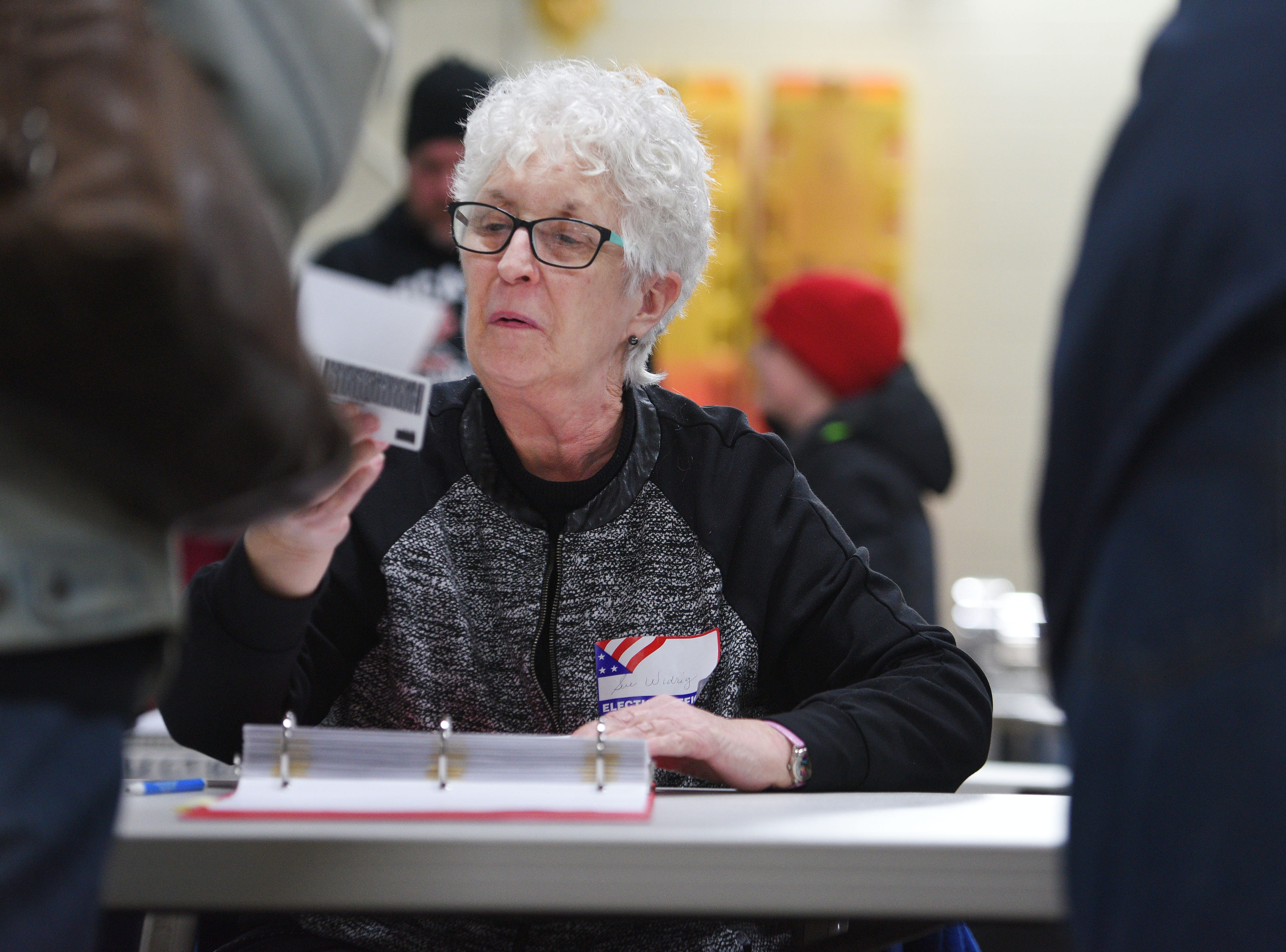 Sue Widrig, poll worker, looks up a voter for the 2018 midterm elections Tuesday, Nov. 6, at Fire Station #7 in Sioux Falls.