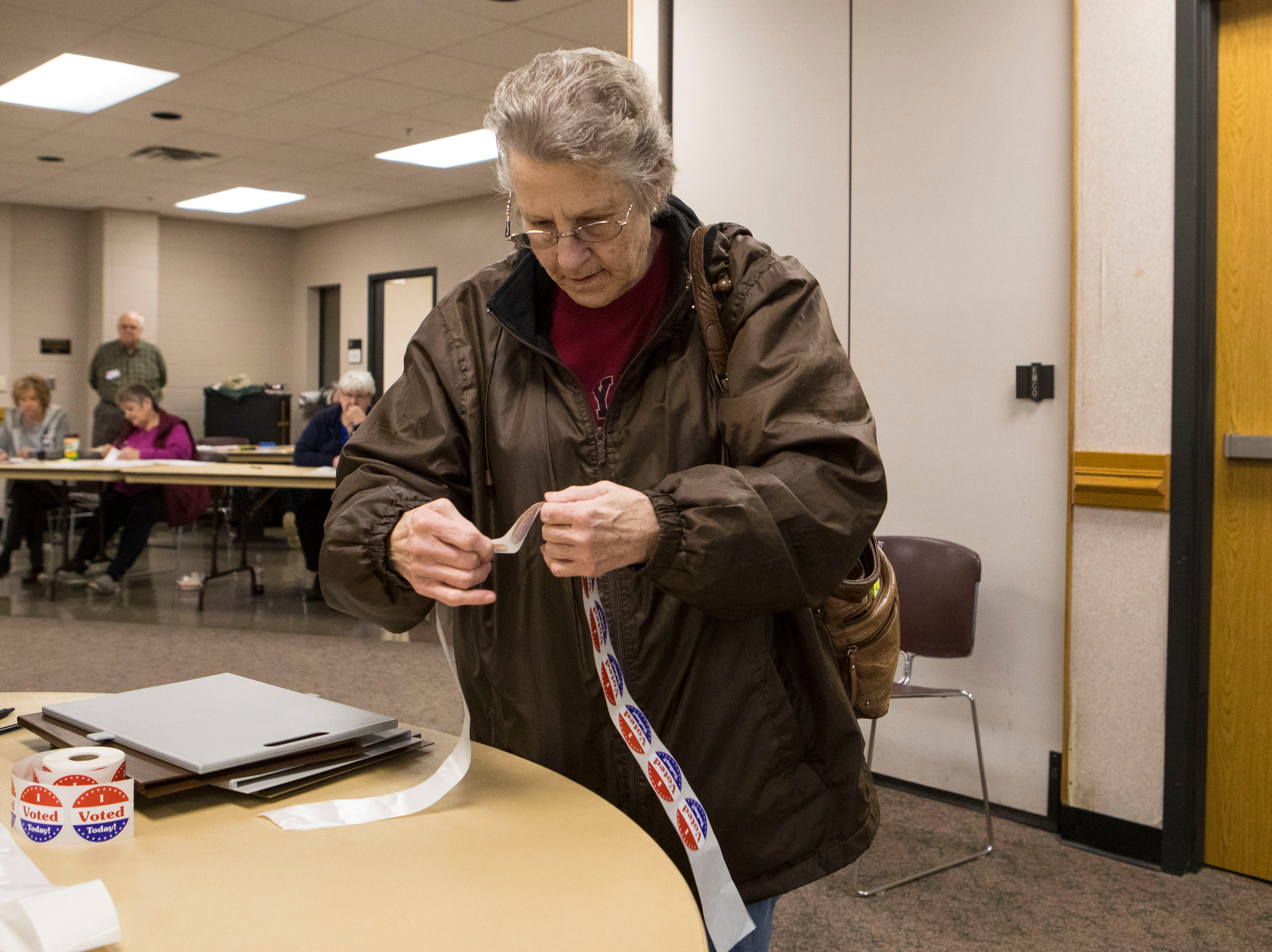 """Diana Friedrichs puts her """"I voted"""" sticker on at First Lutheran Church in Sioux Falls, S.D., Tuesday, Nov. 6, 2018."""