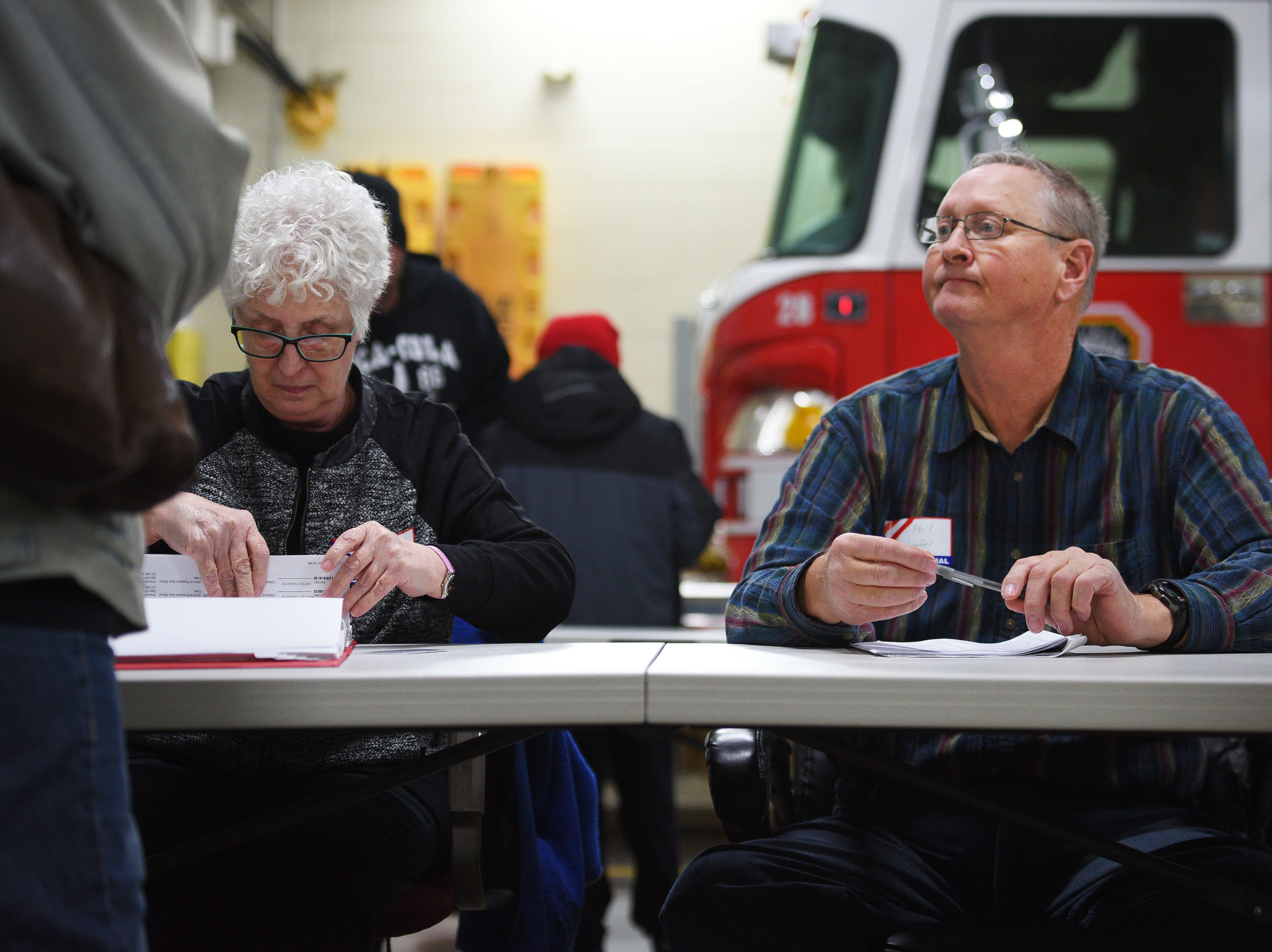 Poll workers Sue Widrig and Phil Schaefer assist voters for the 2018 midterm elections Tuesday, Nov. 6, at Fire Station #7 in Sioux Falls.
