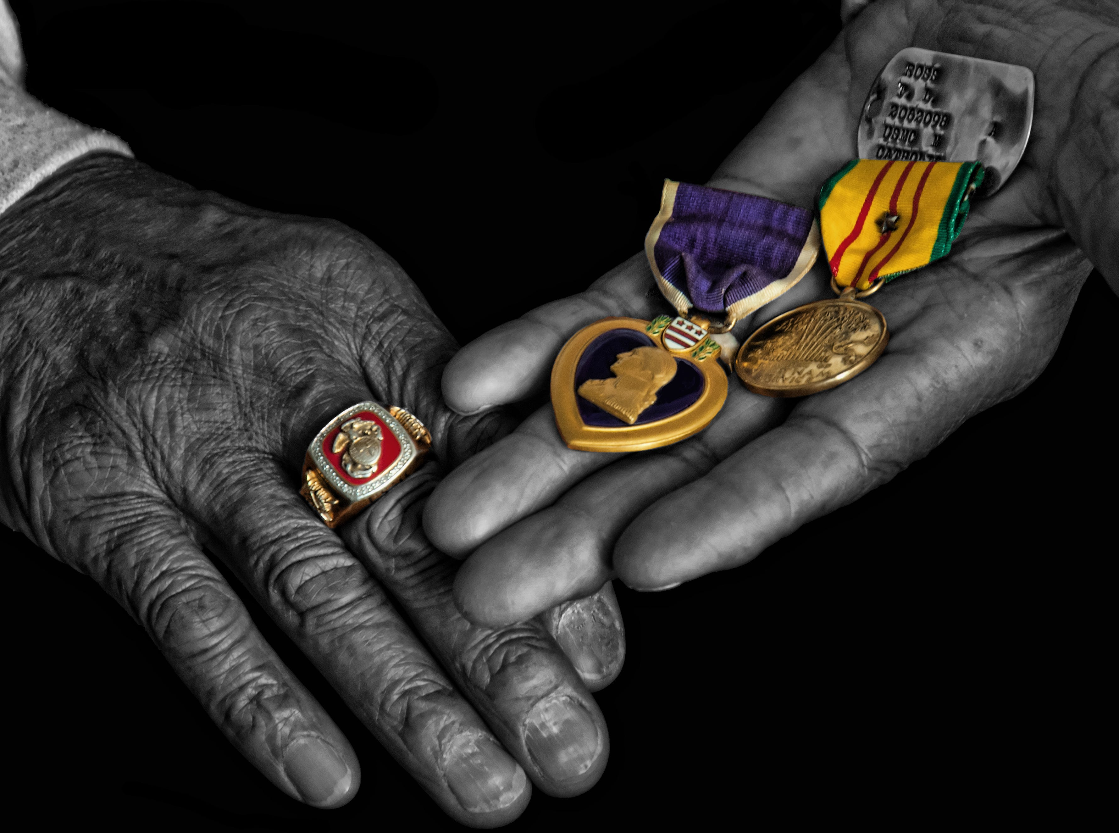 A Vietnam veteran holds the medals he earned while at war.