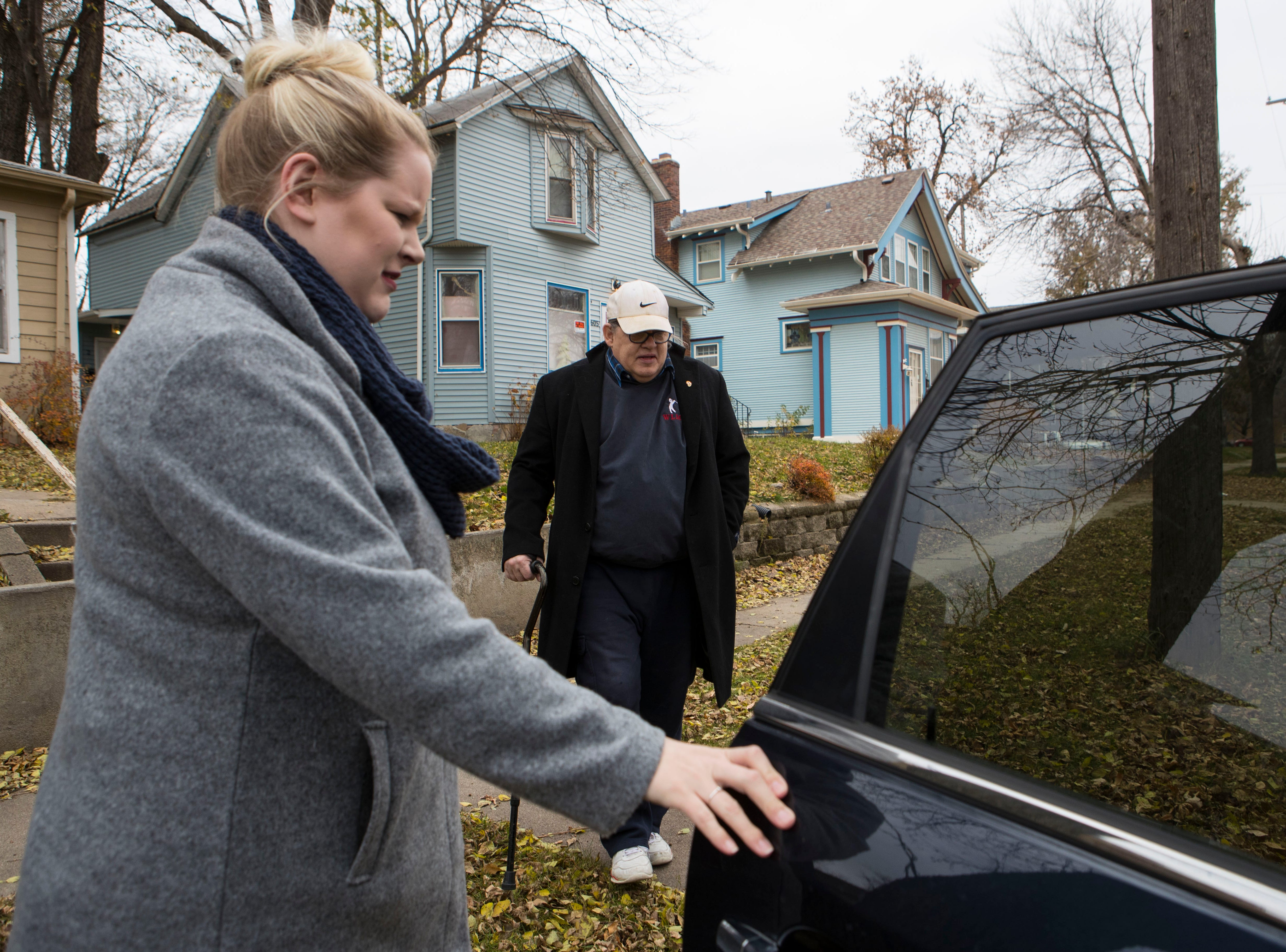 Kirsten Wichern, ACLU volunteer, opens the door for Larry Loebig, in Sioux Falls, S.D., Tuesday, Nov. 6, 2018. The ACLU is offering free rides to people to their voting centers.