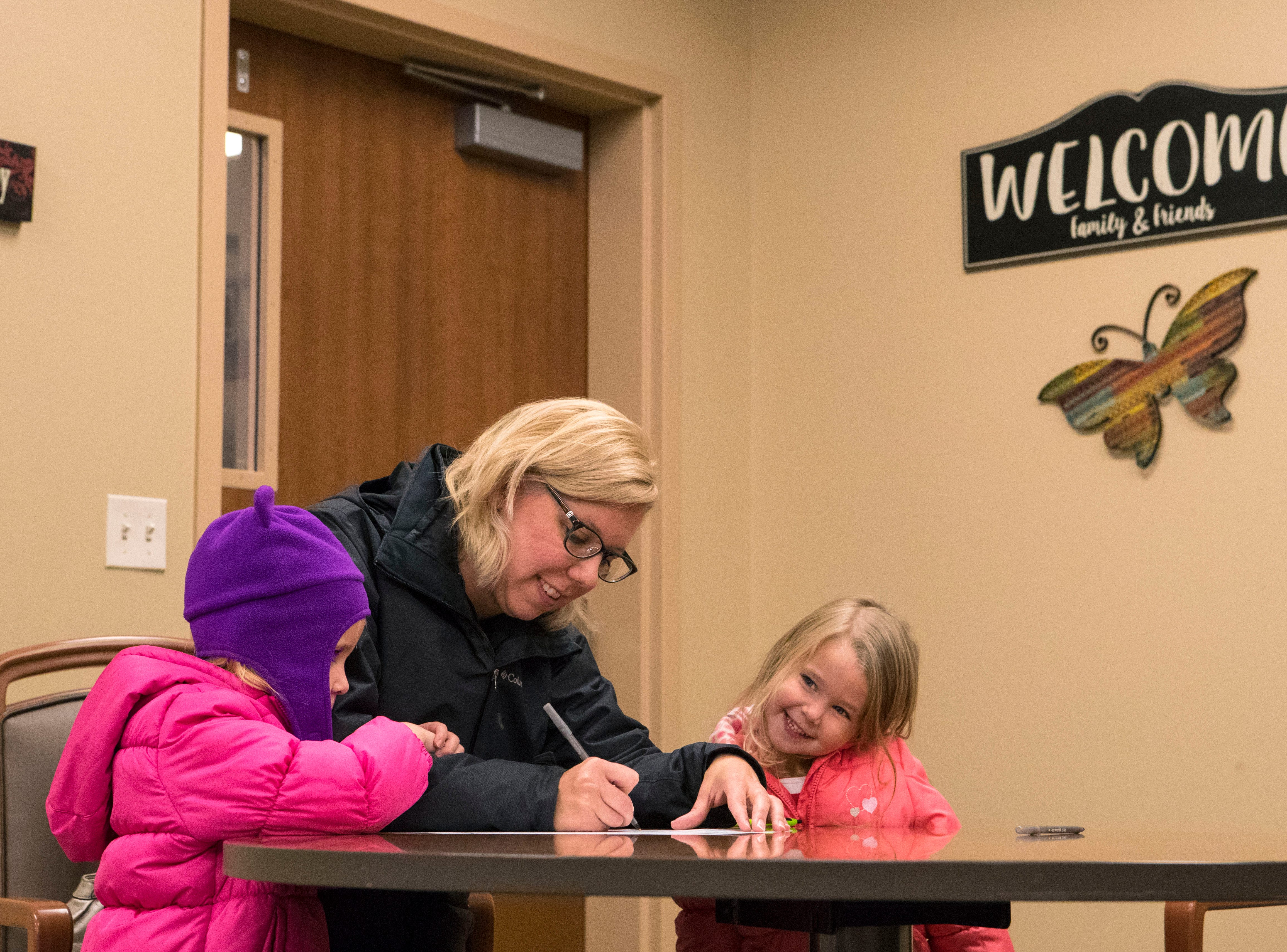 Liza Schnabel fills out her ballot with her daughters Katherine, 3, and Audrey, 4, next to her at Avera Prince of Peace Retirement Community in Sioux Falls, S.D., Tuesday, Nov. 6, 2018.