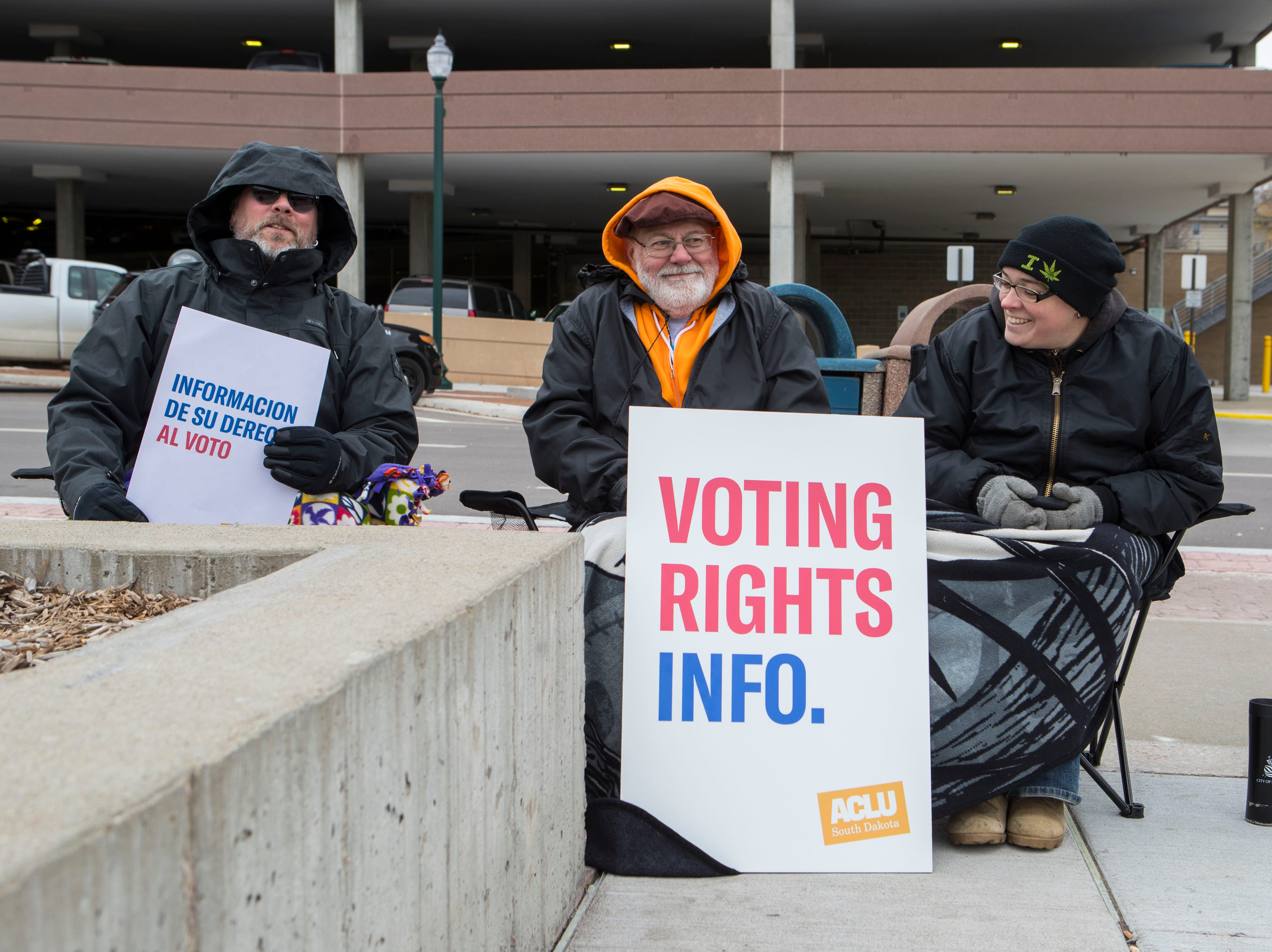 ACLU volunteers Jerry Zeigler Jr. (left to right), Bill Wood and Boots Parker sit outside the Downtown branch of the Siouxland Libraries giving out information to voters in Sioux Falls, S.D., Tuesday, Nov. 6, 2018.