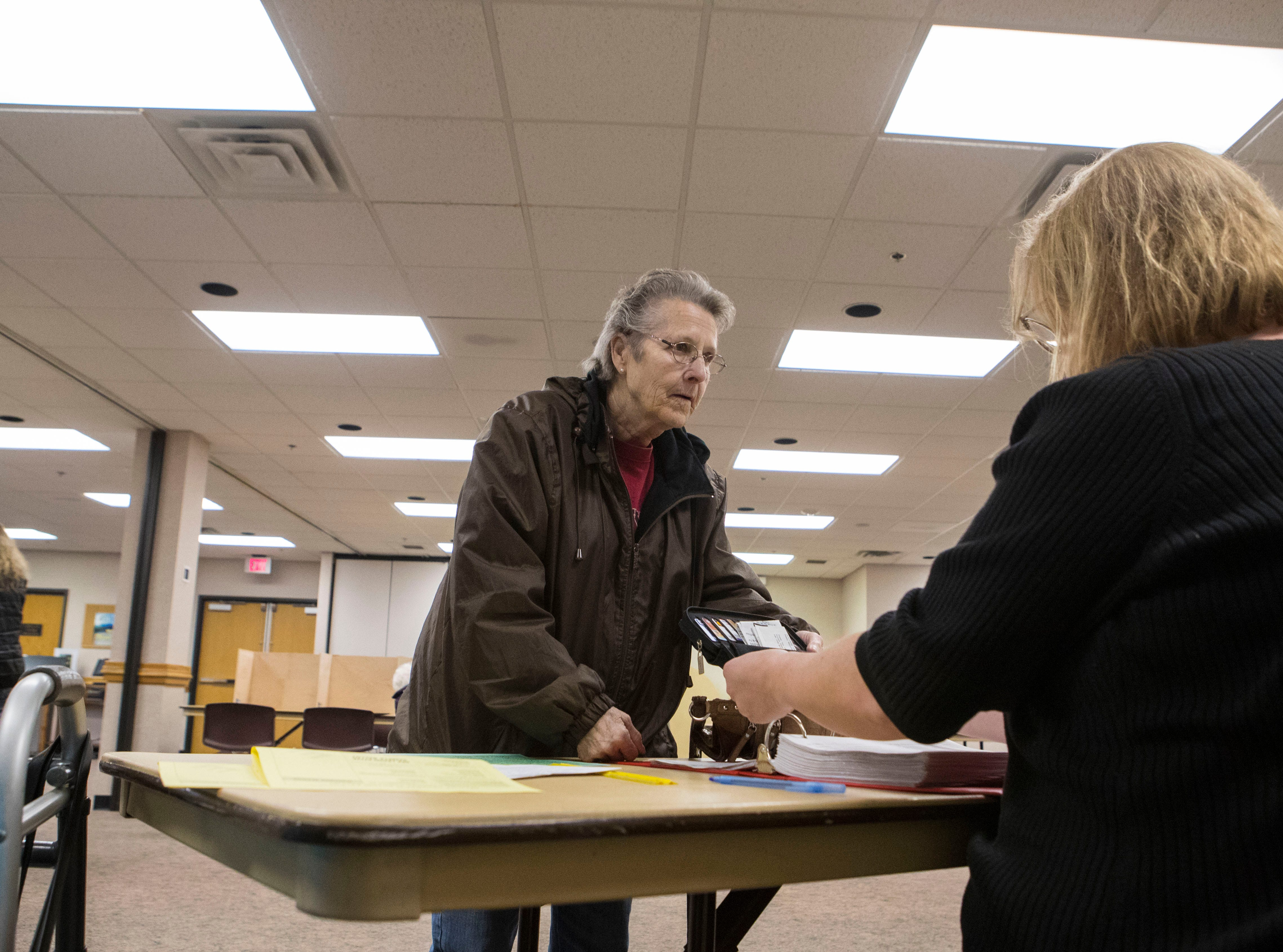 Diana Friedrichs gets checked in by election officials at First Lutheran Church in Sioux Falls, S.D., Tuesday, Nov. 6, 2018.