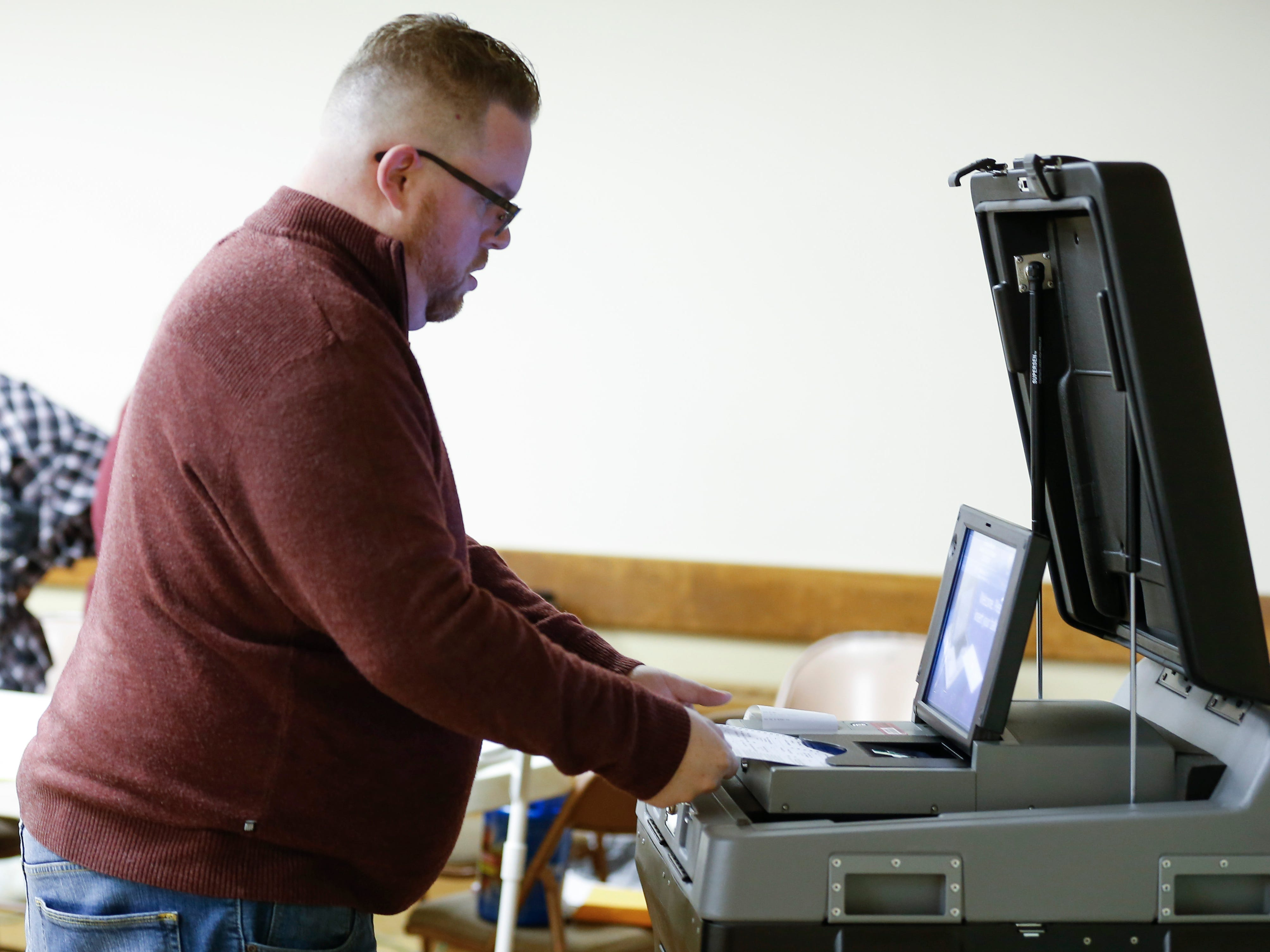 Andy White inserts his ballot into the voting machine at the Woodland Heights polling location on Tuesday, Nov. 6, 2018.