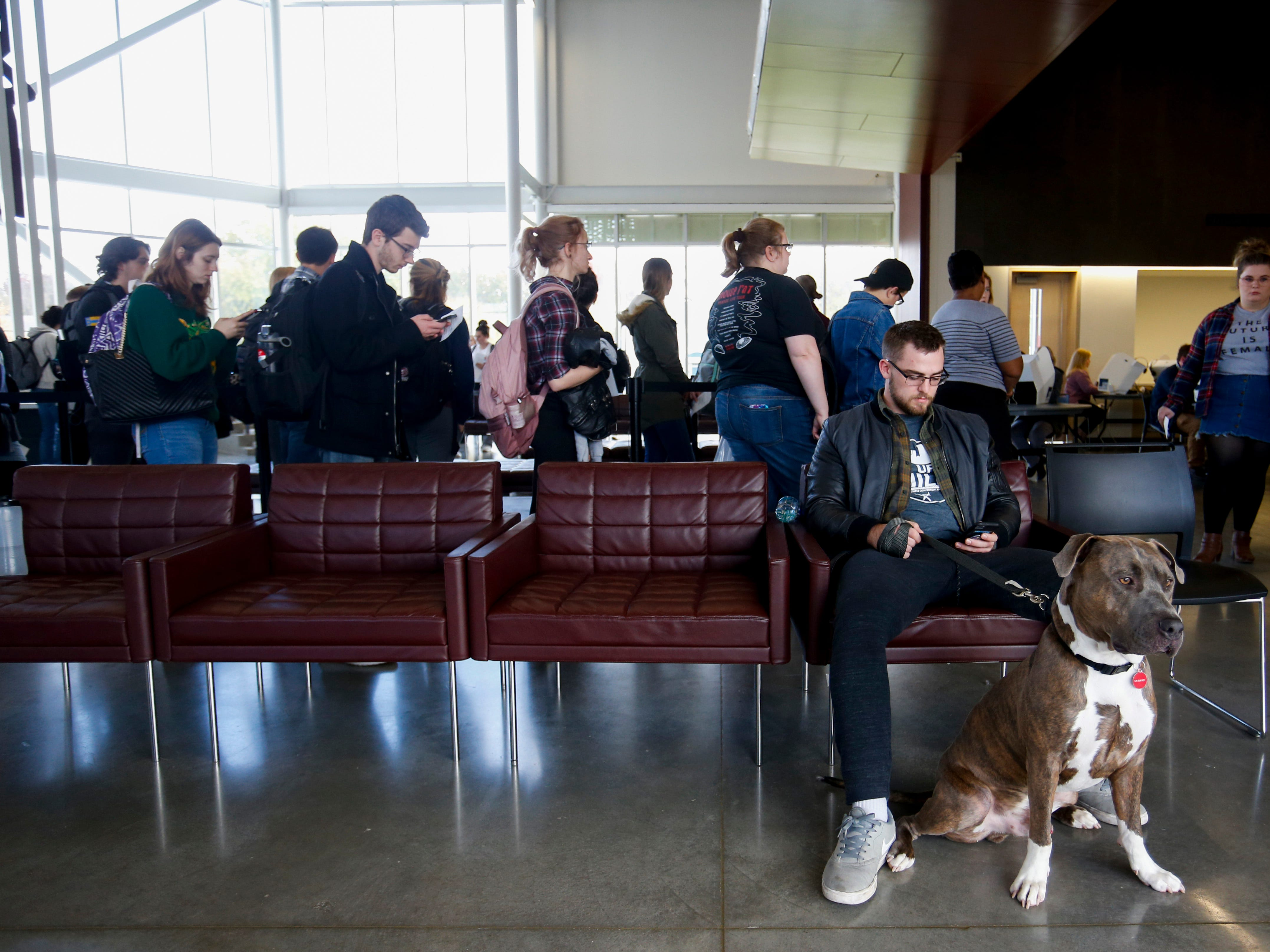 Brett Kellock waits with his dog Tormuned for his girlfriend to vote at the Missouri State University Davis-Harrington Welcome Center on Tuesday, Nov. 6, 2018.