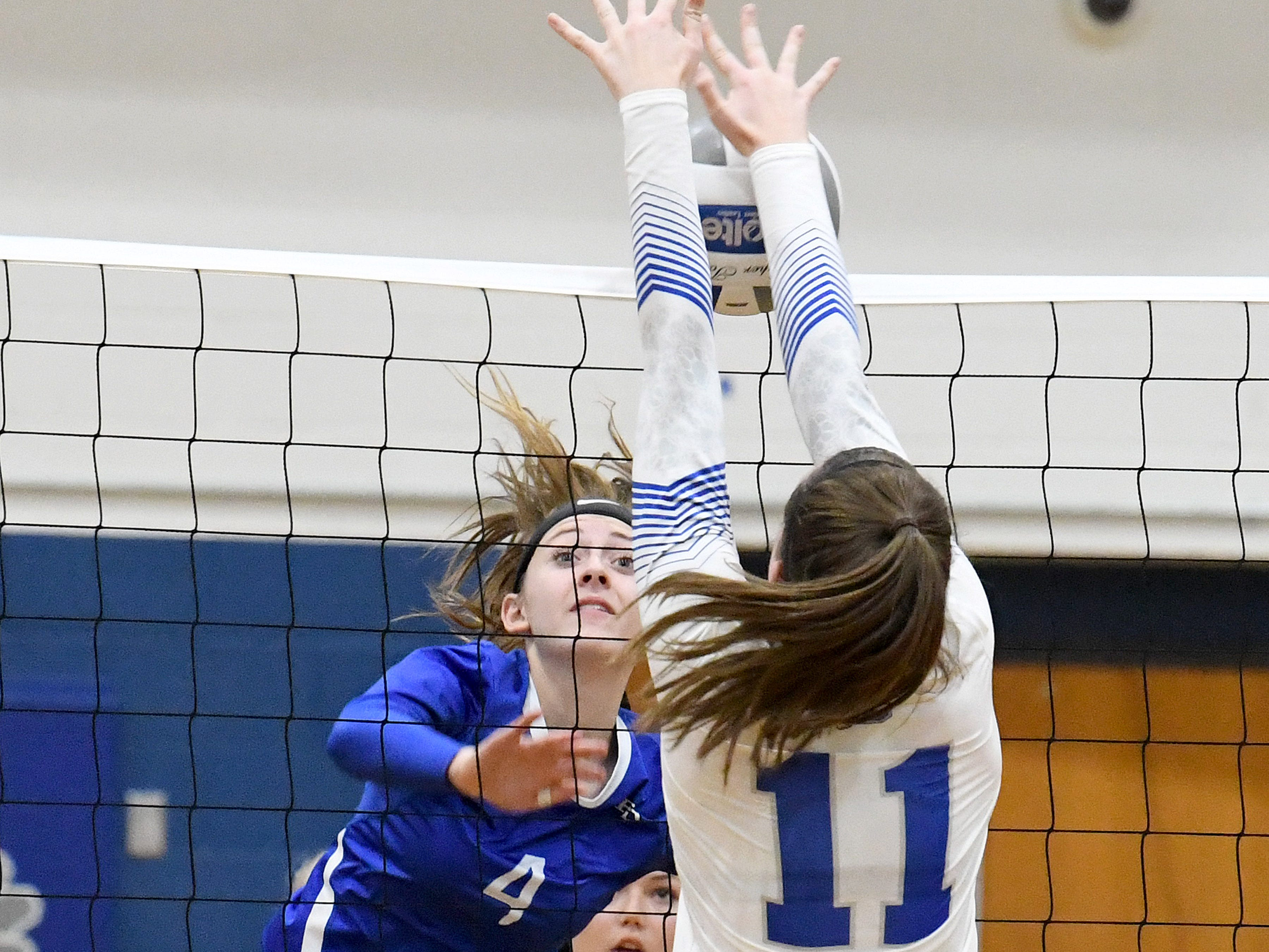 Fort Defiance's Leilani Goggin spikes the ball as Rockbridge County's McKenna Mohler tries to block at the net during a Region 3C semifinal match played in Lexington on Monday, Nov. 5, 2018.