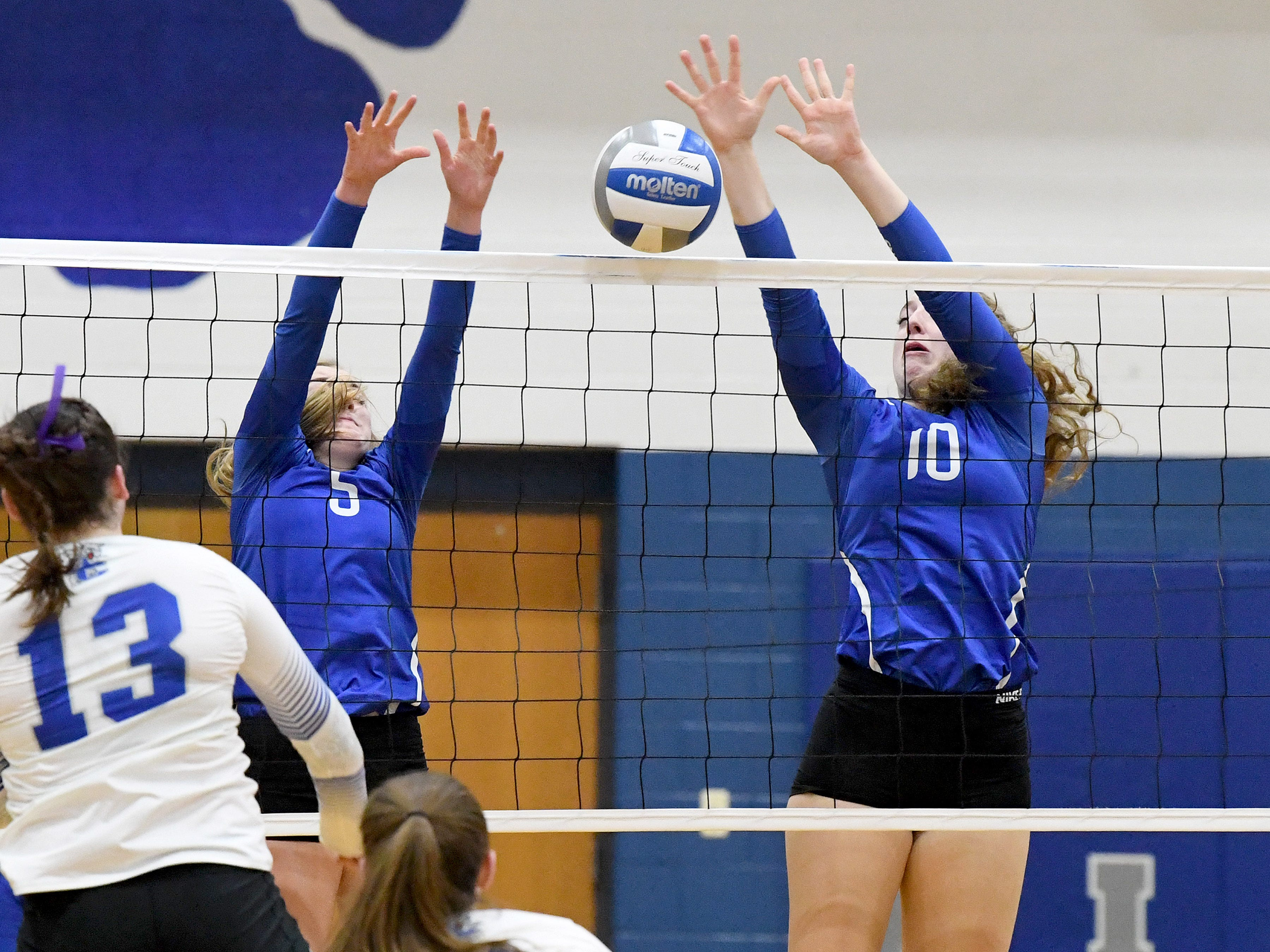 Fort Defiance's Madison Painter and Catie Cramer block a return at the net during a Region 3C semifinal match played in Lexington on Monday, Nov. 5, 2018.