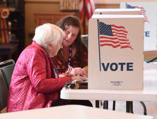 Middlebrook Chief Officer of Election Leslie Piner assists a voter who has vision problems by reading the ballot to her.