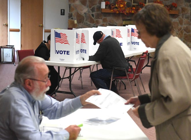 One resident votes while another is handed their ballot at Seventh Day Adventist Church in Staunton on Nov. 6, 2018.