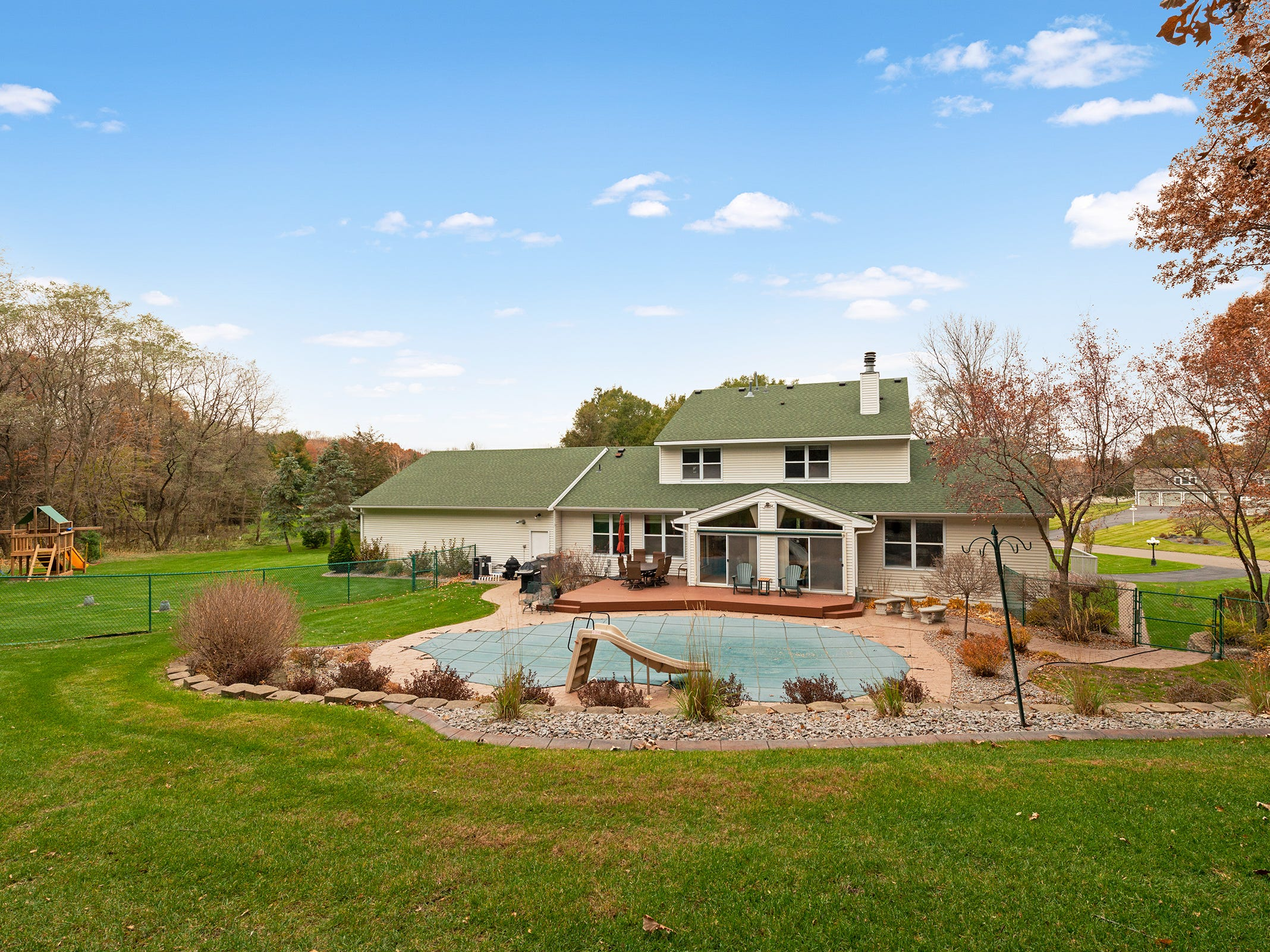 The property includes an in-ground pool, ground-level deck and professional landscaping.