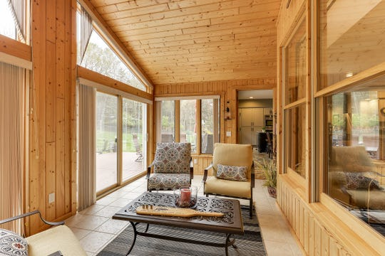 The great room looks through to the three-season porch with its vaulted ceilings and wood-paneled walls.