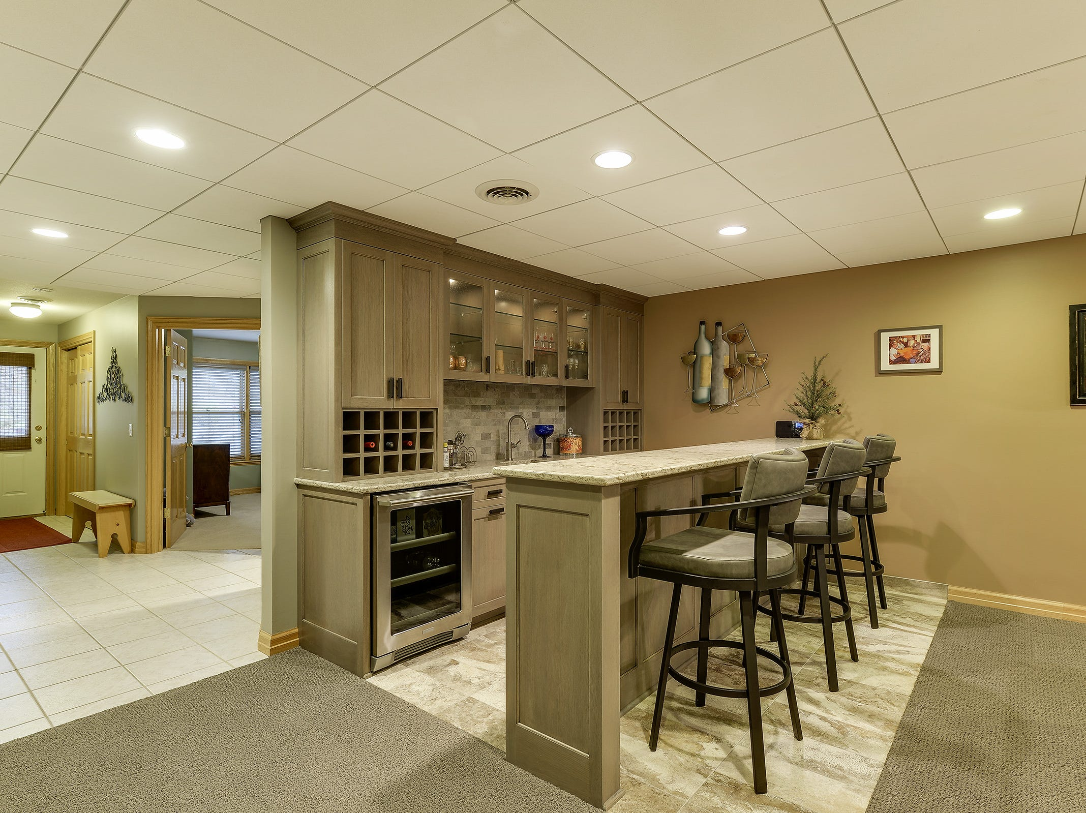The wet bar has space for barstool seating and has a wine fridge along with a generous amount of storage and cabinetry.