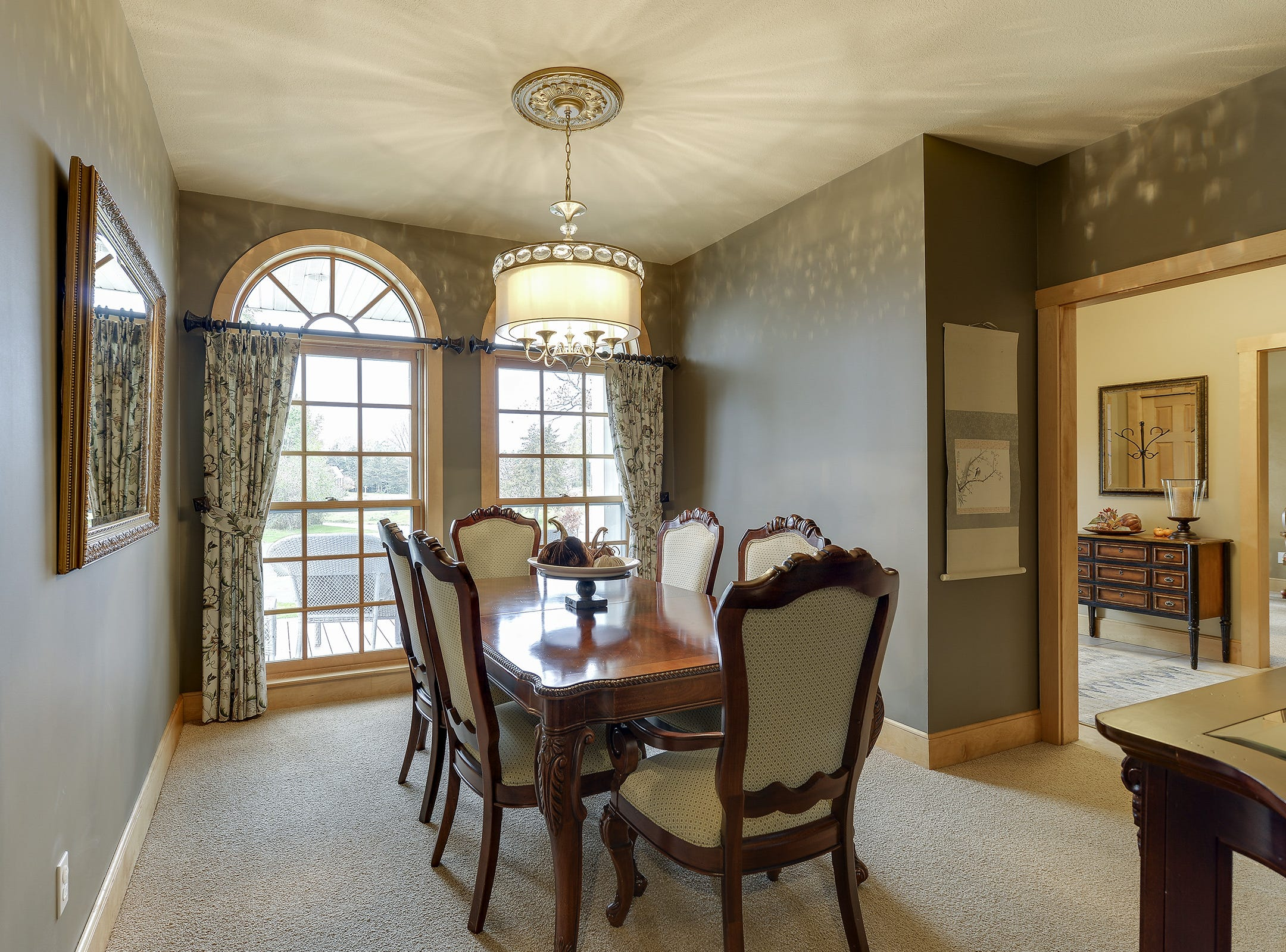The formal dining room has floor-to-ceiling and wall-to-wall arched windows to let in the natural light of the outdoors.