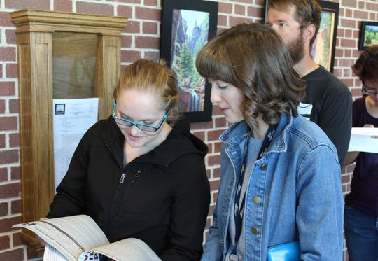Cedar City voters Deborah Ferwerda and Jessica Sannar take a last look at the voting guide while waiting in line Election Day Nov. 6, 2018.