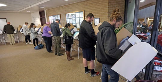 People cast their ballots at a polling station Tuesday, Nov. 6, 2018, in Salt Lake City.