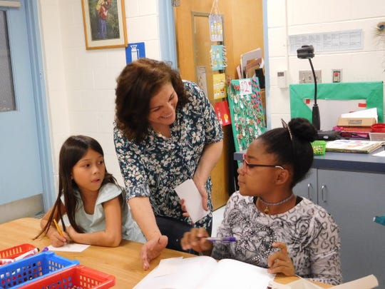 Wafa Elsaka works with her after-school art club students to help them process feelings related to the hurricane.